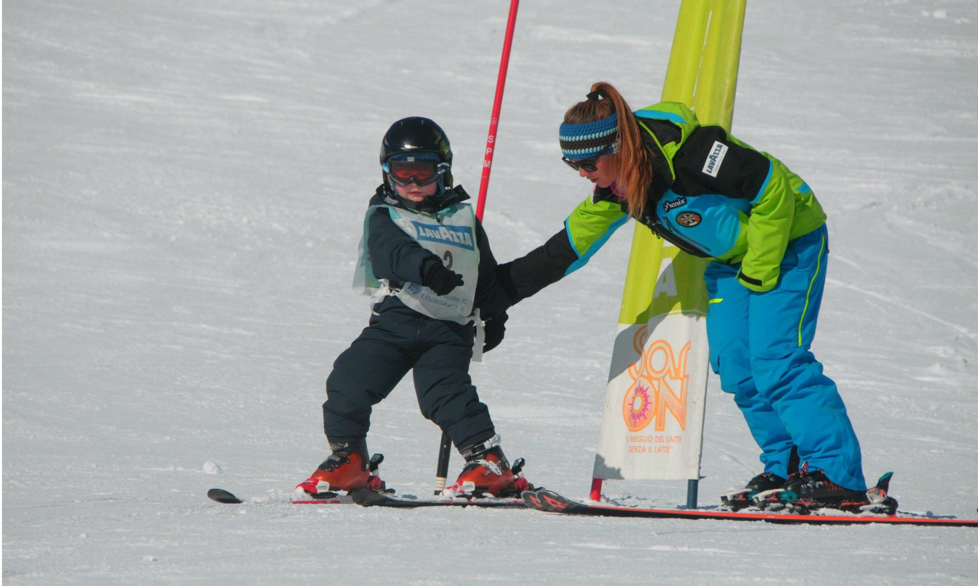 Una maestra di sci guida un bambino attraverso gli ostacoli sulla pista.