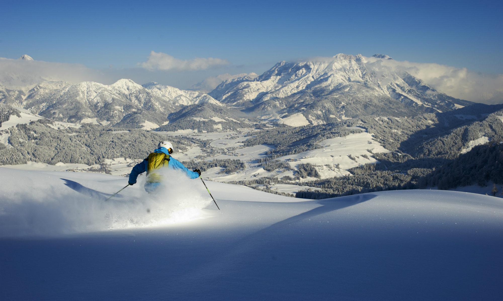 Een freestyle skiër is bezig aan een afdaling in de diepe poedersneeuw in Fieberbrunn.