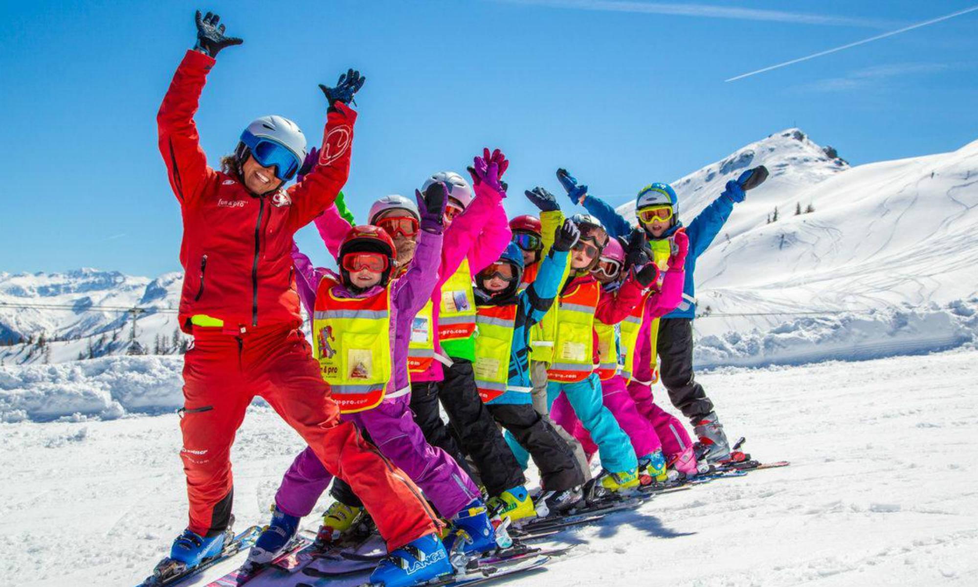 Een groep blije kinderen tijdens een skiles met hun leraar op een zonnige helling in Flachau.