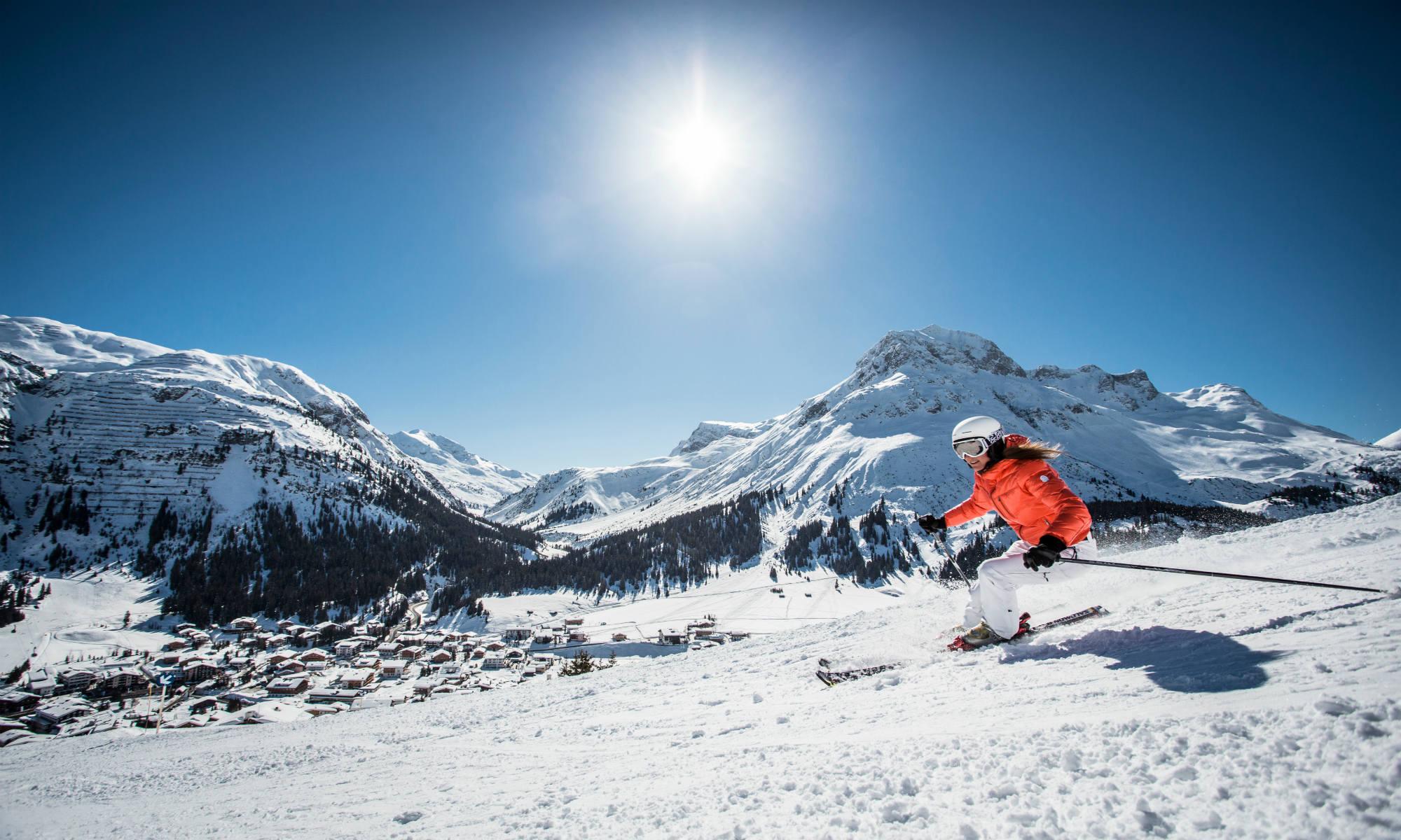 1 skiër in actie, met het prachtige sneeuwlandschap van Lech op de achtergrond.