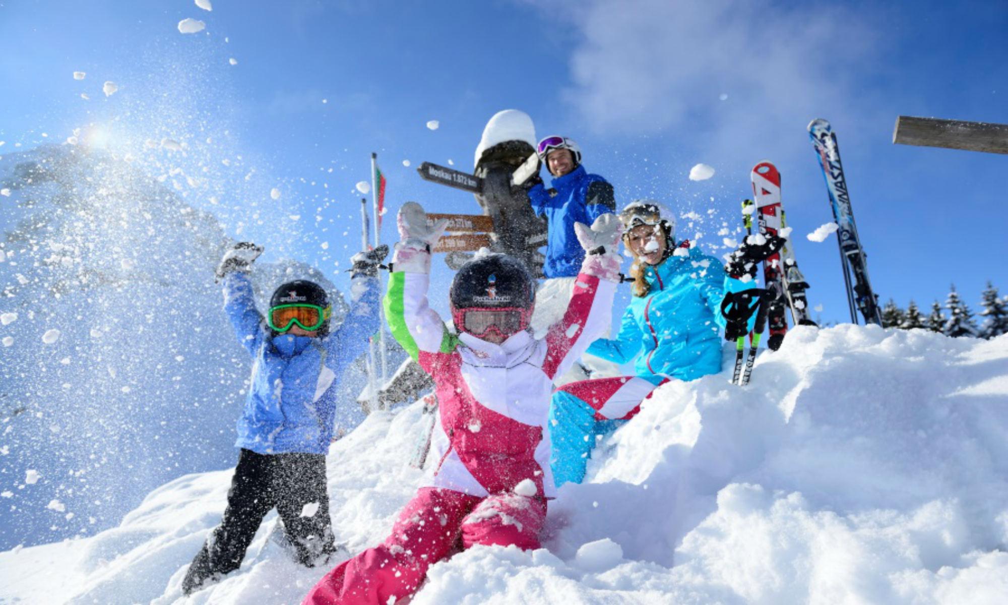 Een groep kinderen geniet van de diepe poedersneeuw in de Kitzbüheler Alpen.