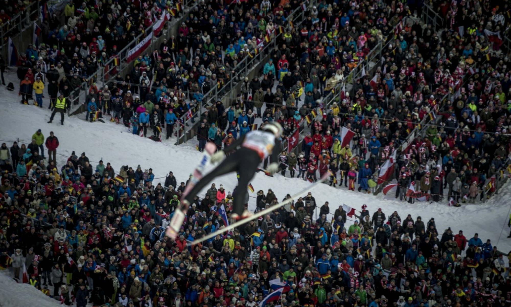 Skispringer beim Absprung von der Skiflugschanze in Oberstdorf vor einer Menschenmasse.