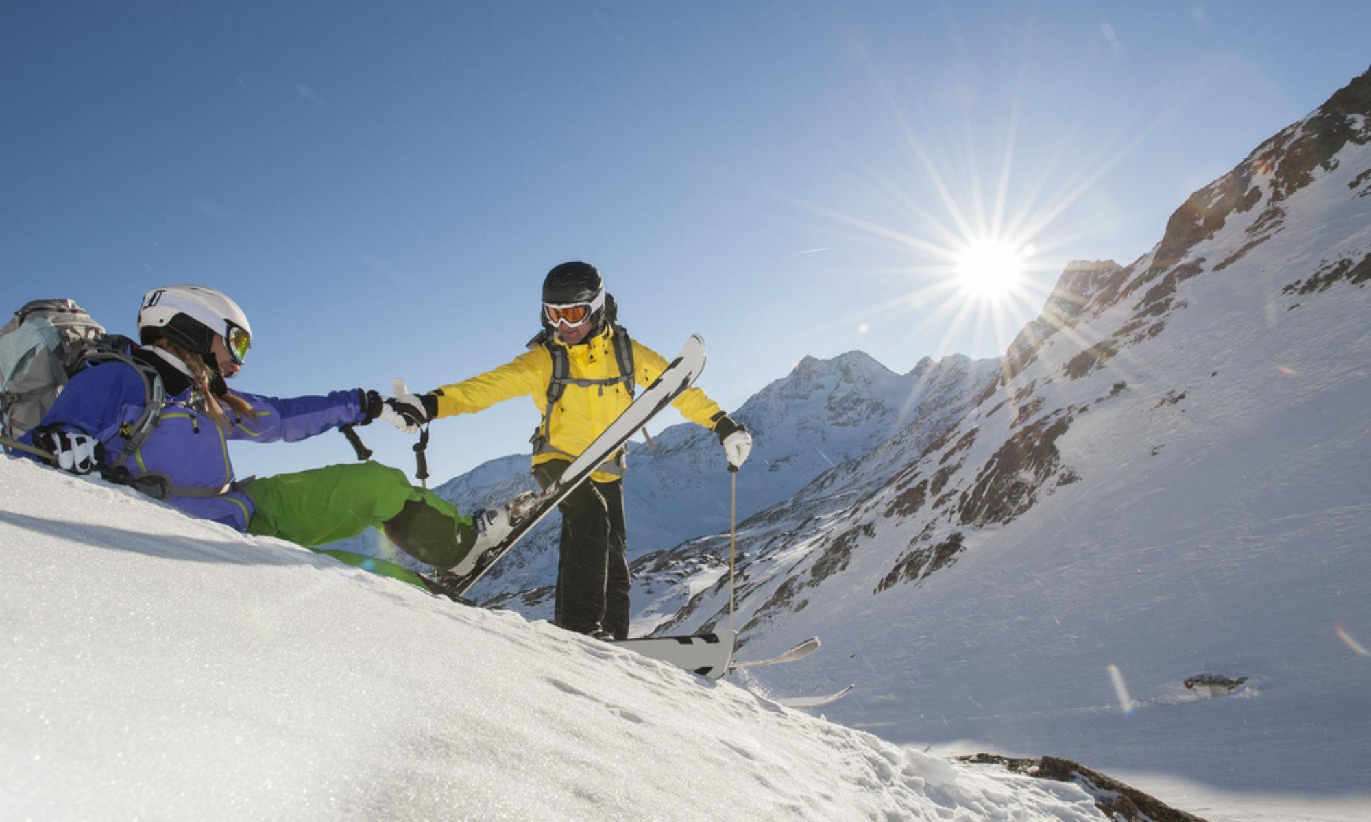 Ein Skifahrer hilft einer gestürzten Skifahrerin beim Wiederaufstehen.