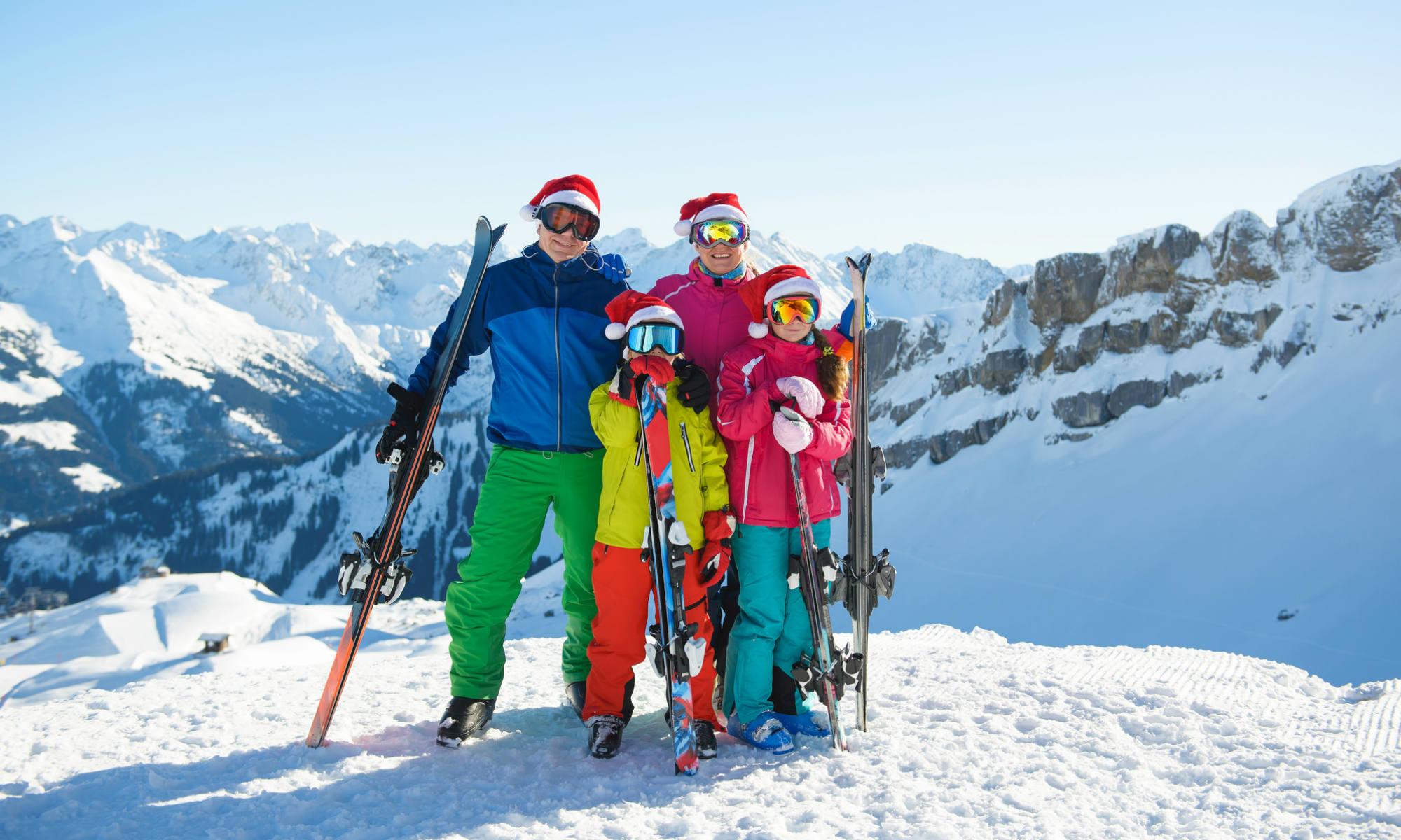 Eine Familie mit Weihnachtsmützen auf einer sonnigen Skipiste