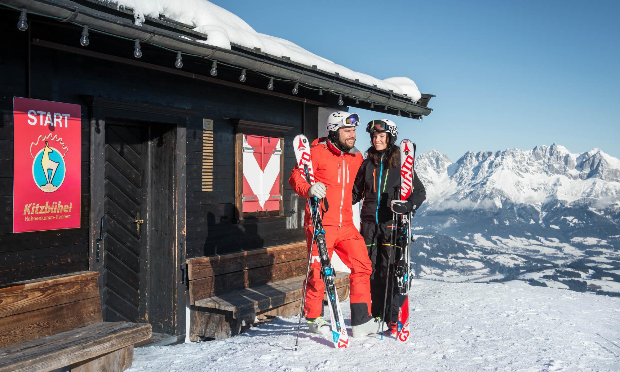2 erwachsene Skifahrer bei einer traditionellen Berghütte im Skigebiet KitzSki in Kitzbühel.