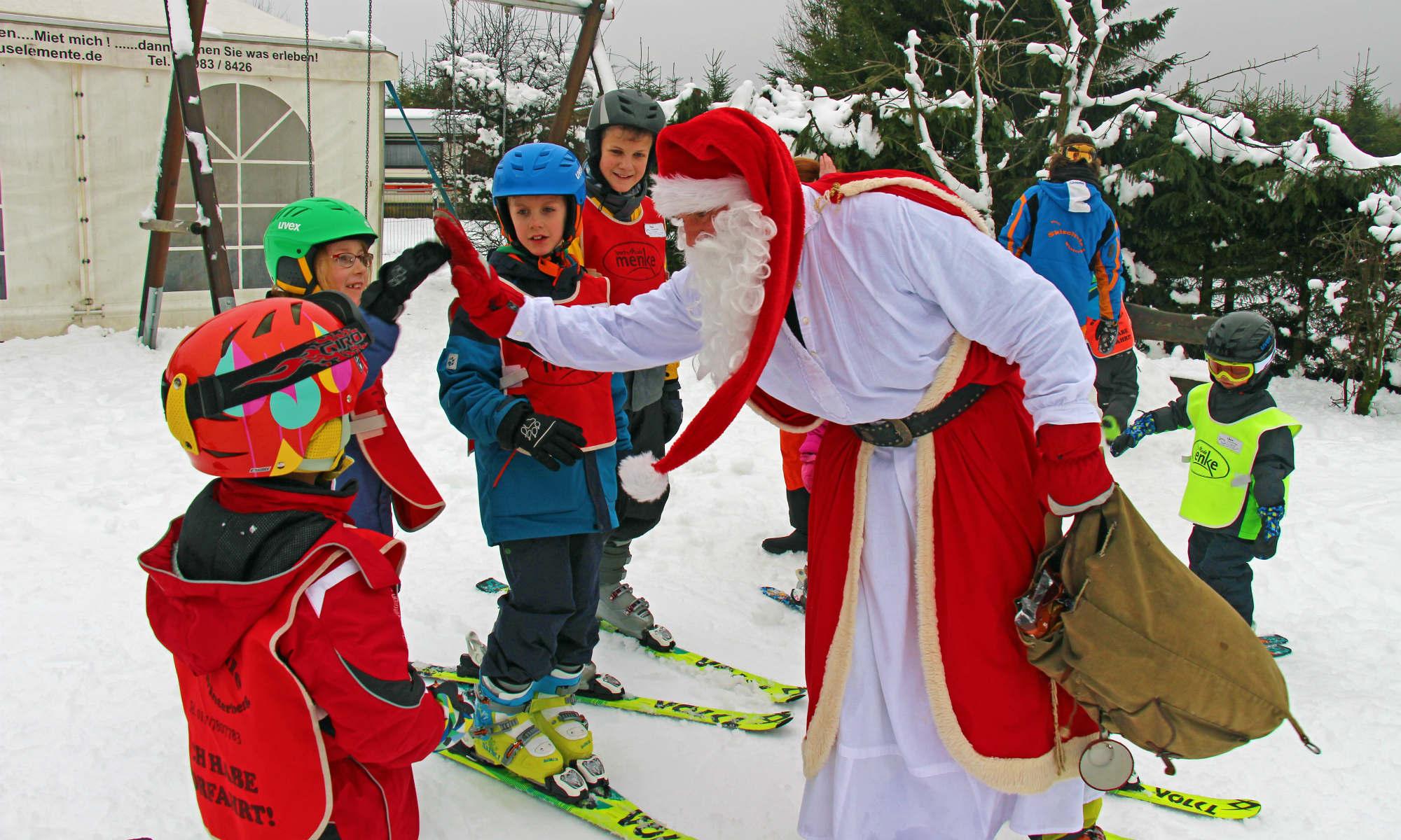 Kinder werden beim Skikurs vom Weihnachtsmann besucht.