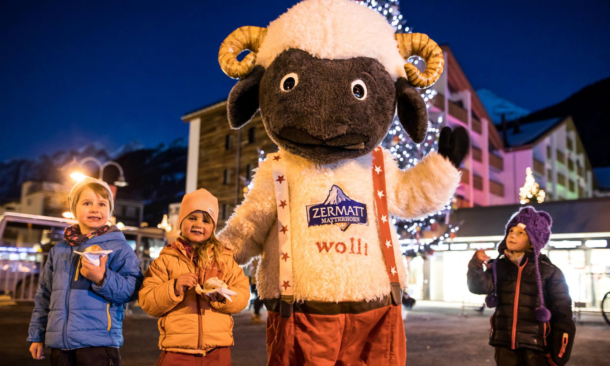 Das Maskottchen Wolli und drei Kinder bei der Weihnachtsfeier im Skigebiet Zermatt.