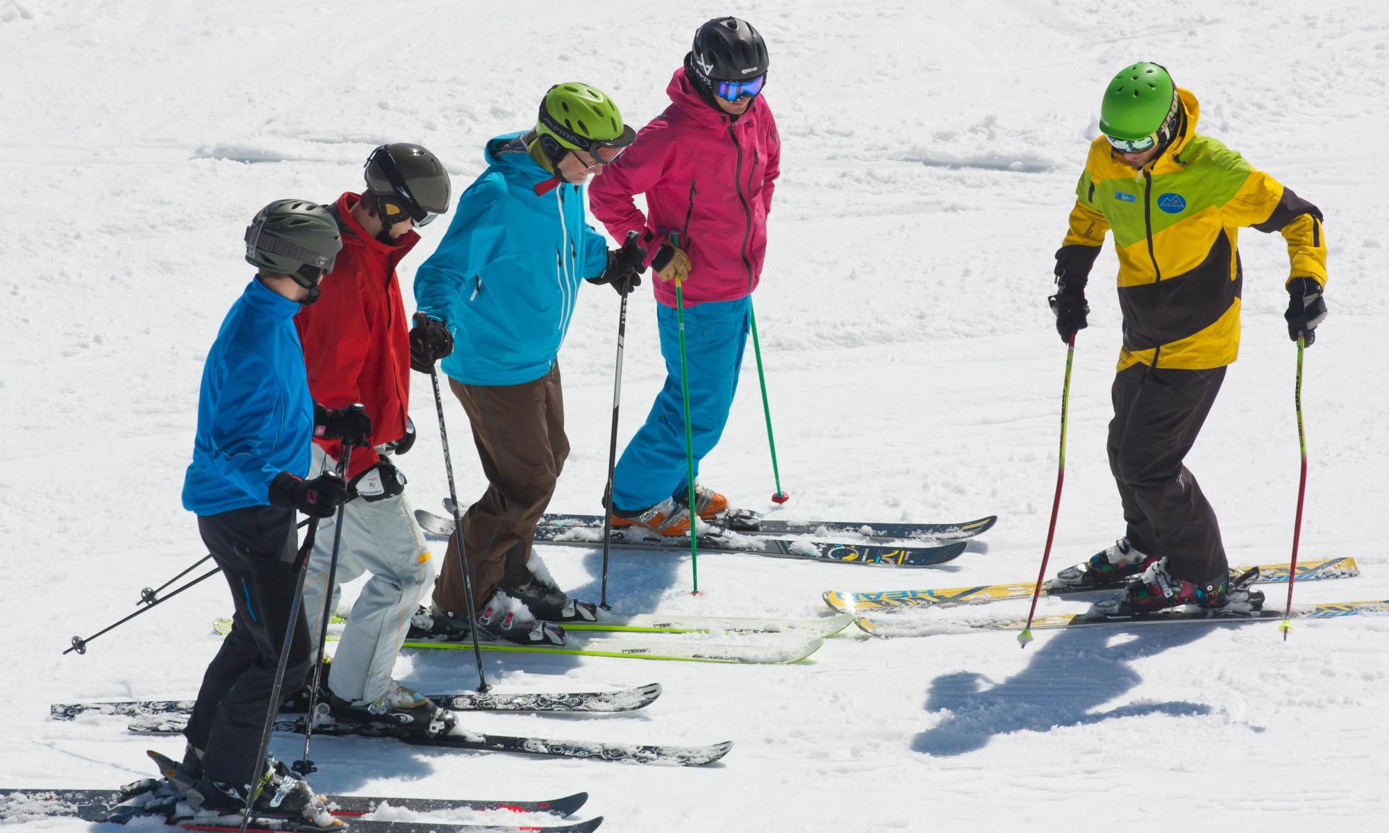 Ein Skilehrer der Skischule Montevia erklärt 4 Erwachsenen die Skitechnik.