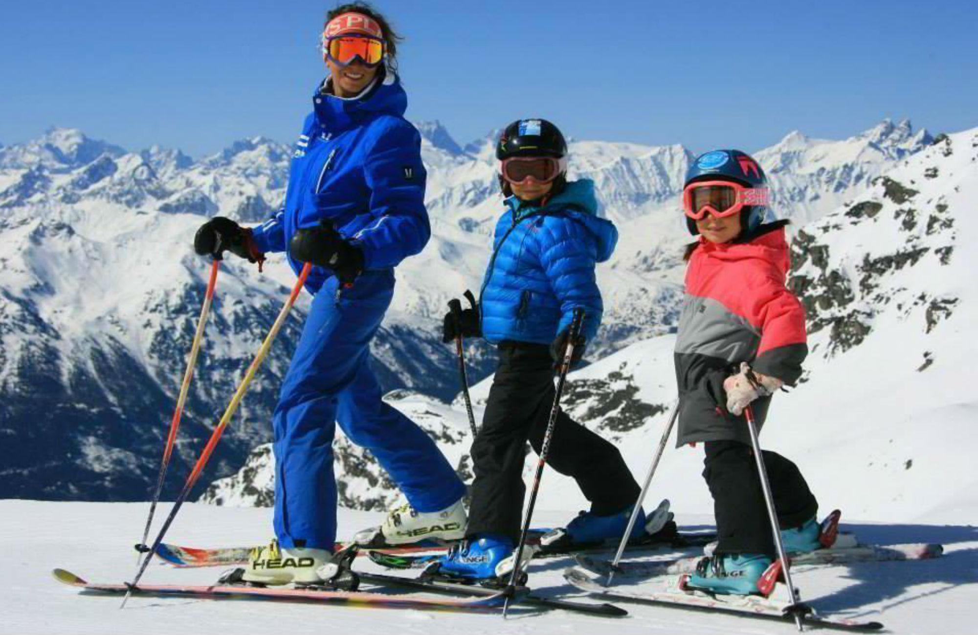 Skilehrerin posiert gemeinsam mit 2 Kindern vor dem Bergpanorama des Skigebiets Les 3 Vallées.