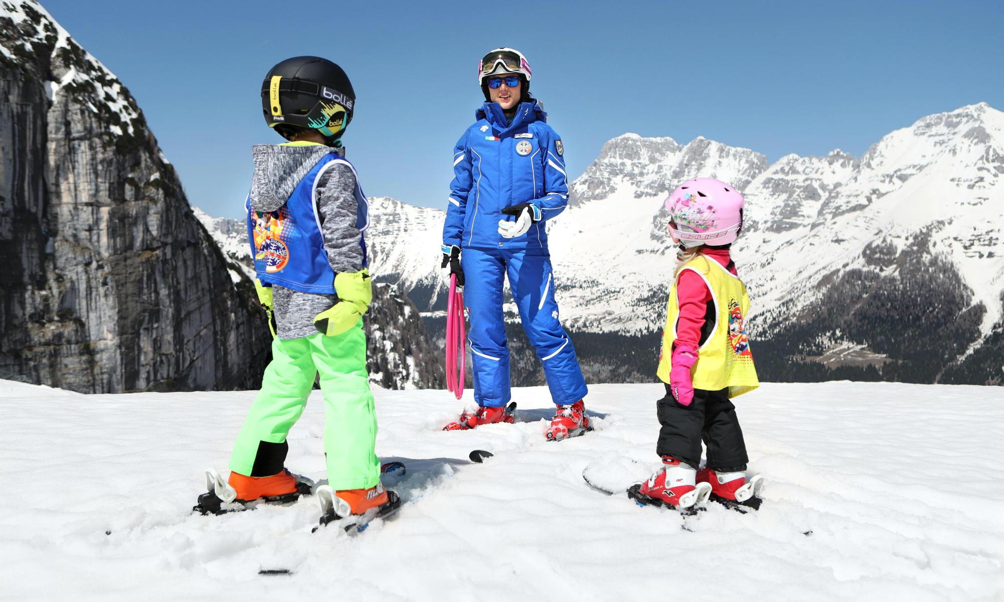 Eine Skilehrerin erklärt 2 Kindern die Skitechnik auf einer sonnigen Piste in Madonna di Campiglio.