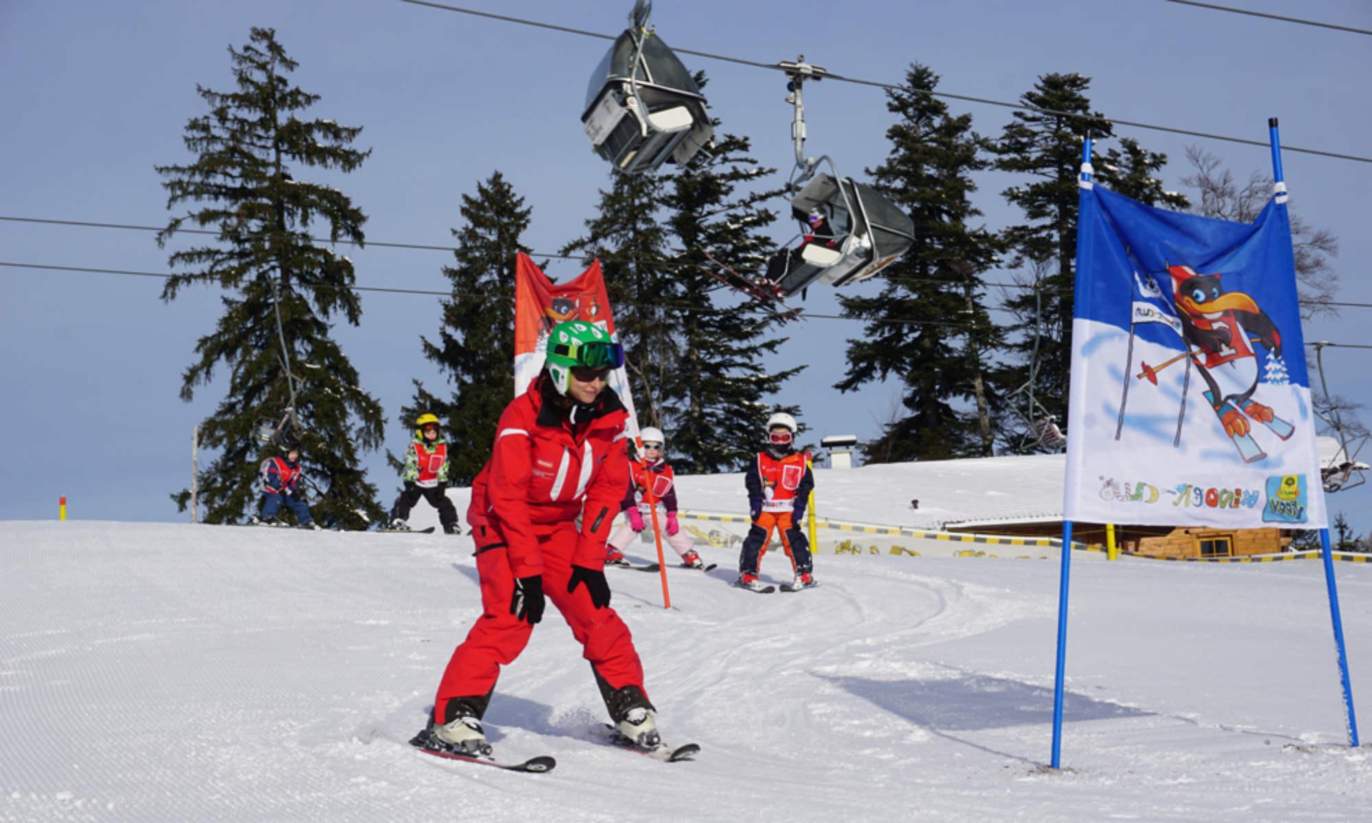Eine Skilehrerin bringt Kindern im Kinderland das Kurvenfahren im Pflug bei.