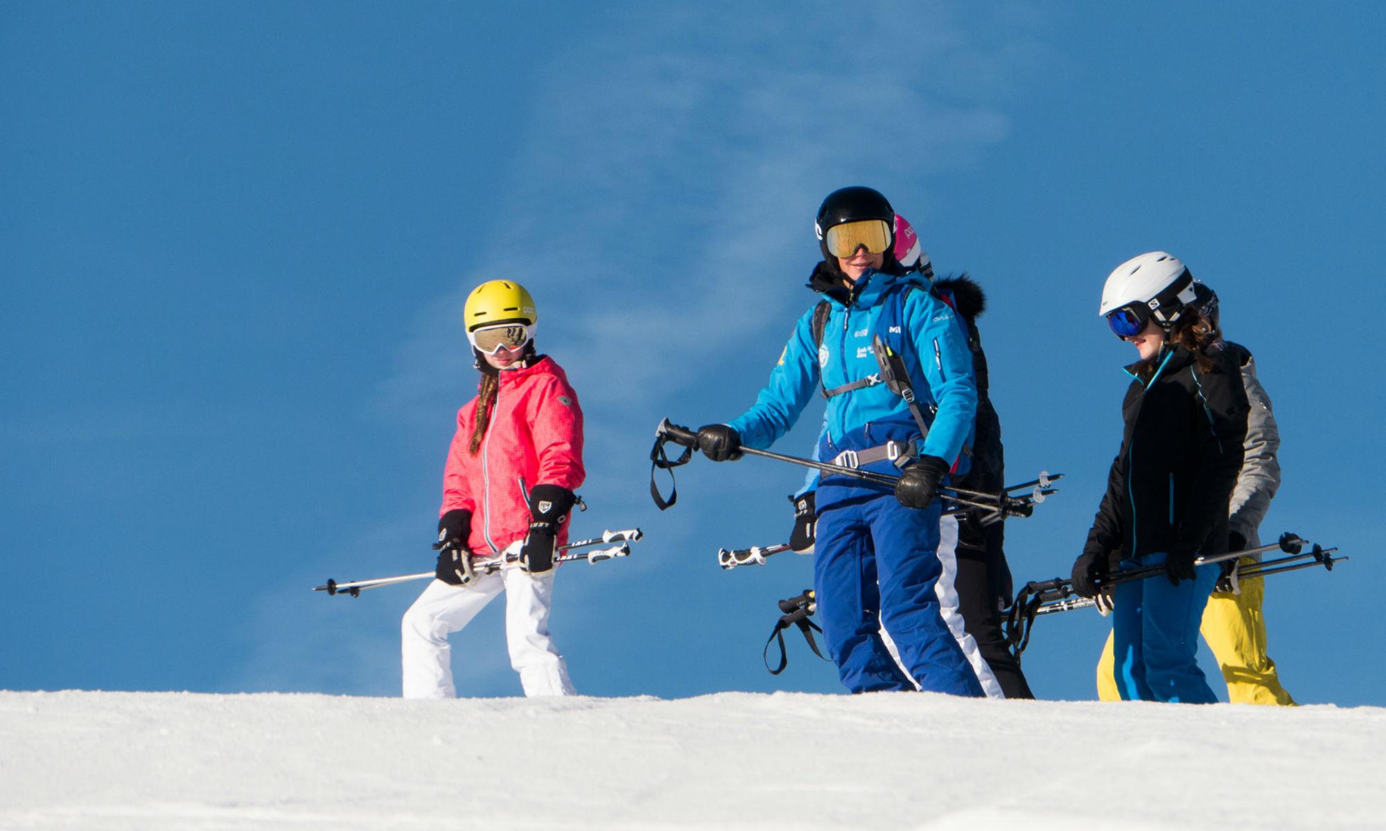 Eine Skilehrerin mit 4 Teenagern auf der sonnigen Skipiste.