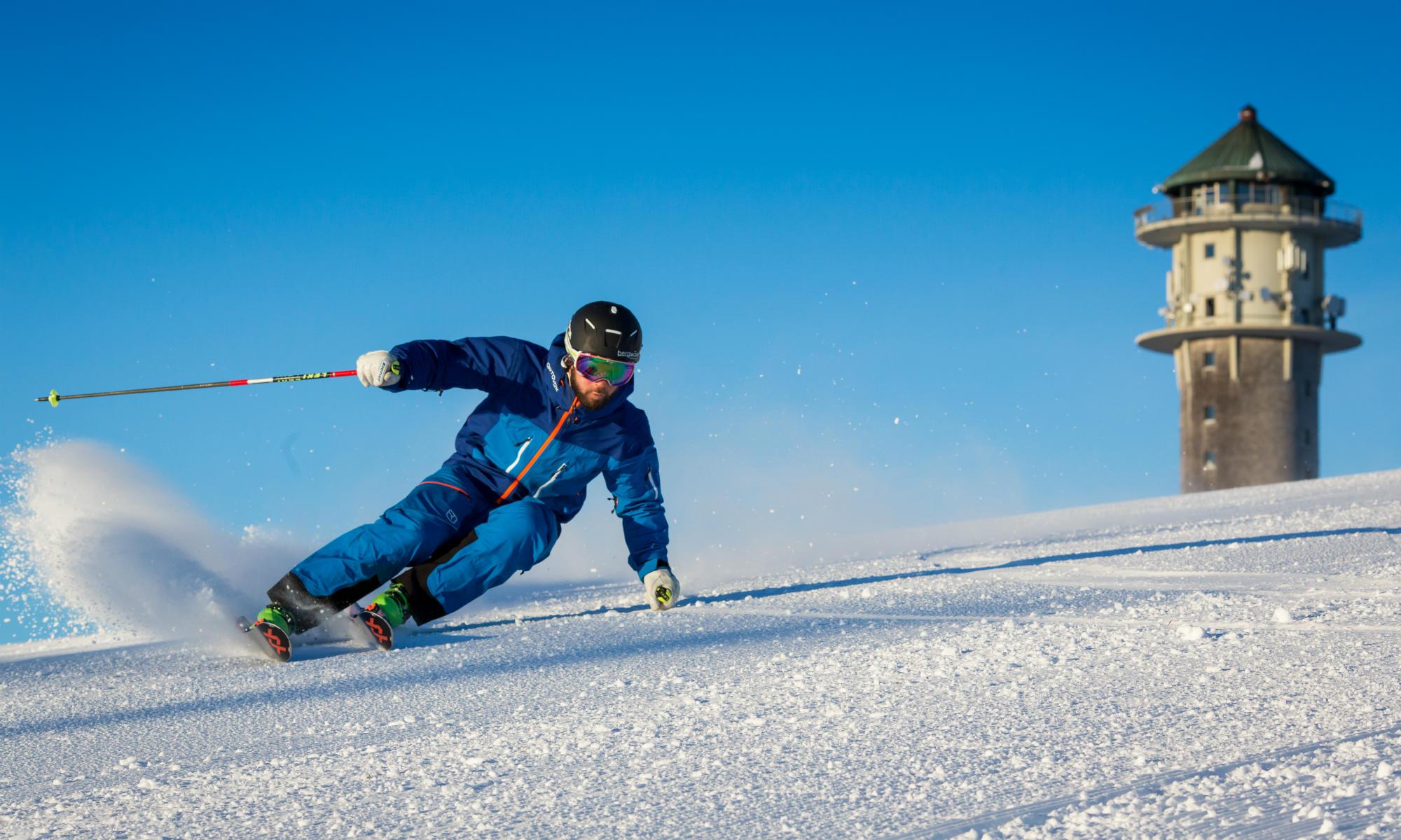 Skifahrer auf einer sonnigen Piste am Feldberg im Schwarzwald.