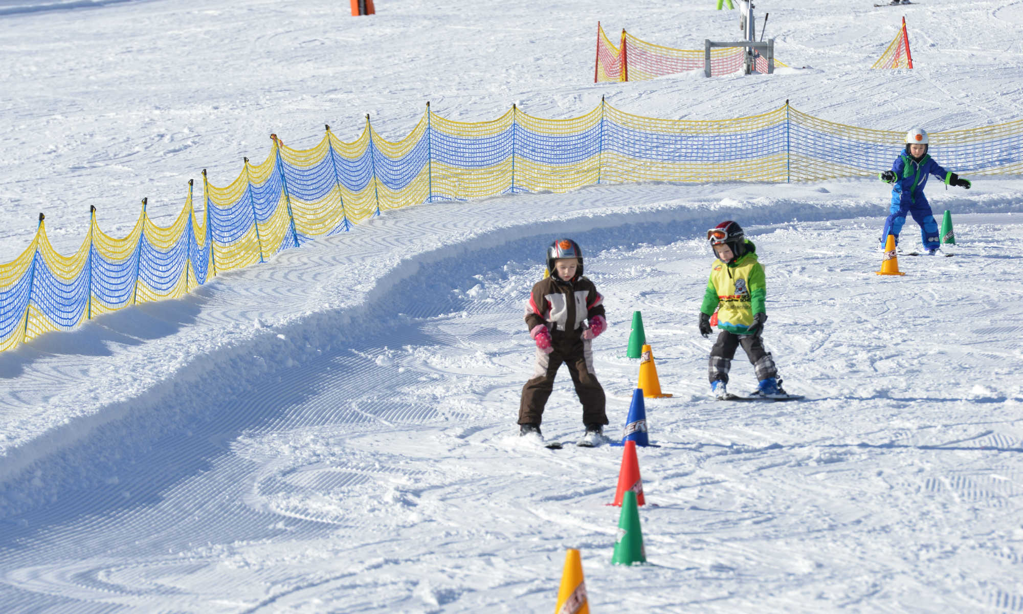 Drei Kinder üben das Kurvenfahren in einem Übungsgelände am Brauneck in Lenggries.