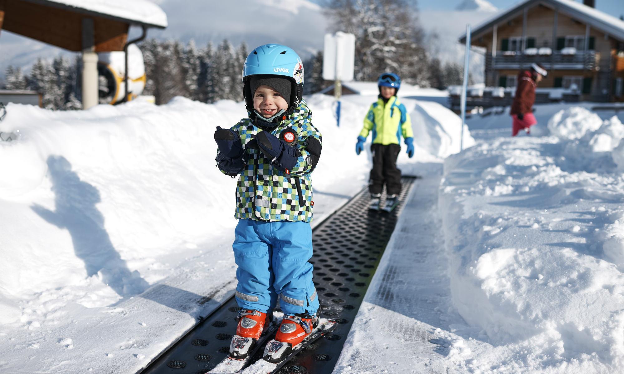 Kinder auf dem Förderband im Kinderland Söllis Winterwelt im Skigebiet Oberstdorf.