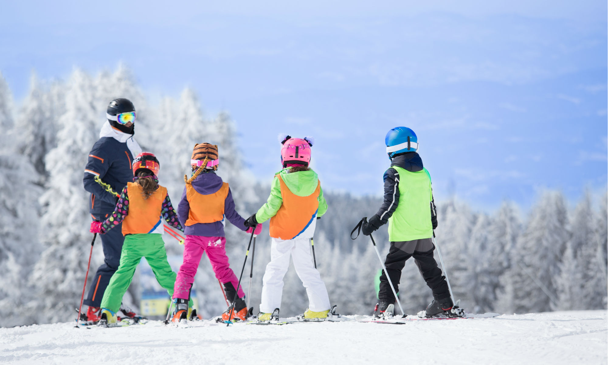 Ein Skilehrer bringt 4 Kindern das Skifahren in Feldberg bei.