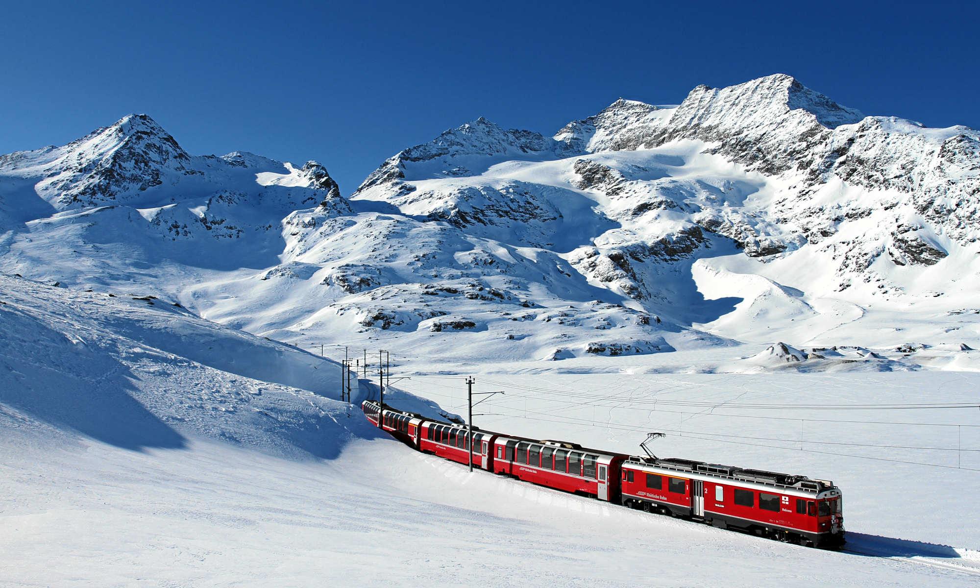 Der Bernina Express fährt entlang des Lago Bianco in den Schweizer Alpen.