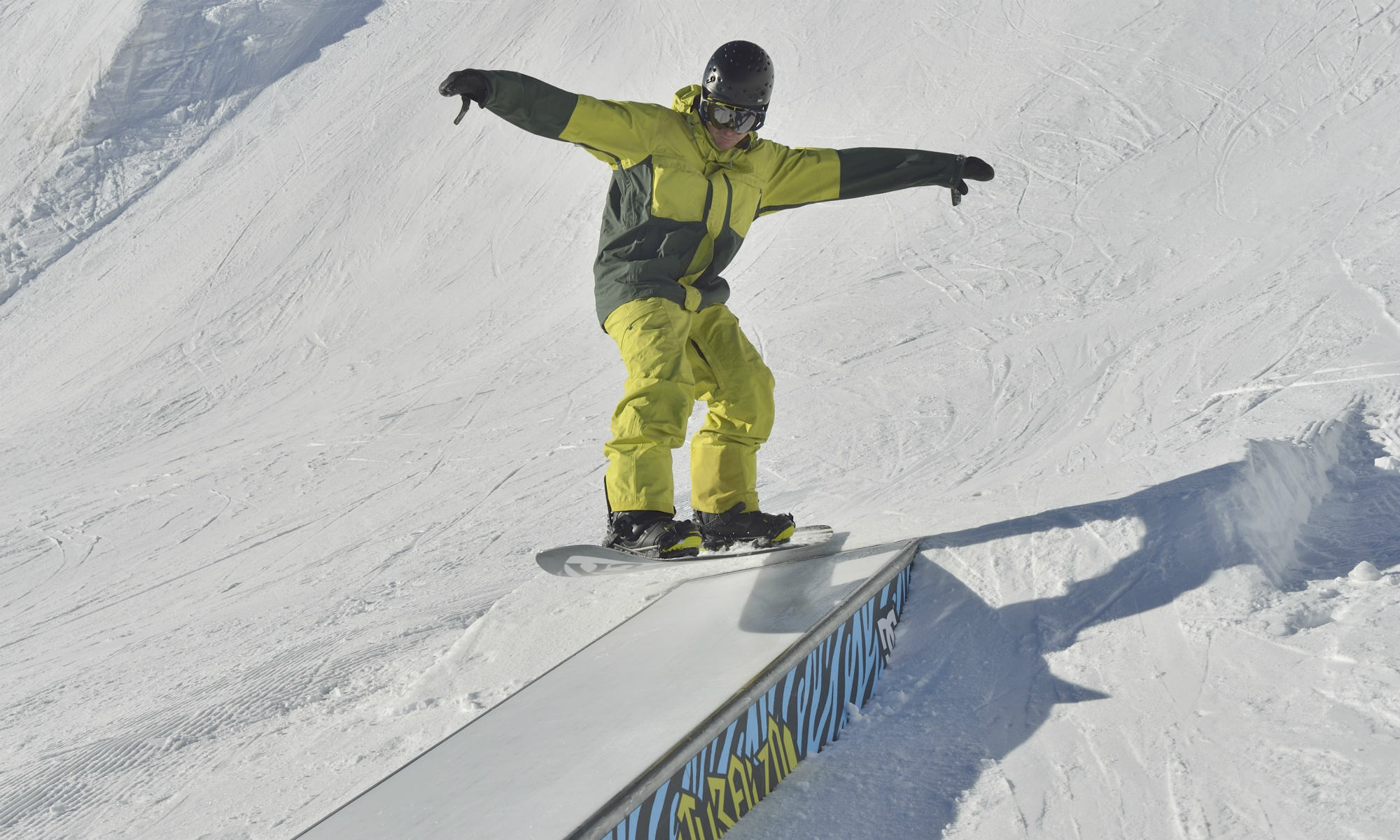 Ein Snowboarder fährt über eine Box in einem Funpark in Nendaz.
