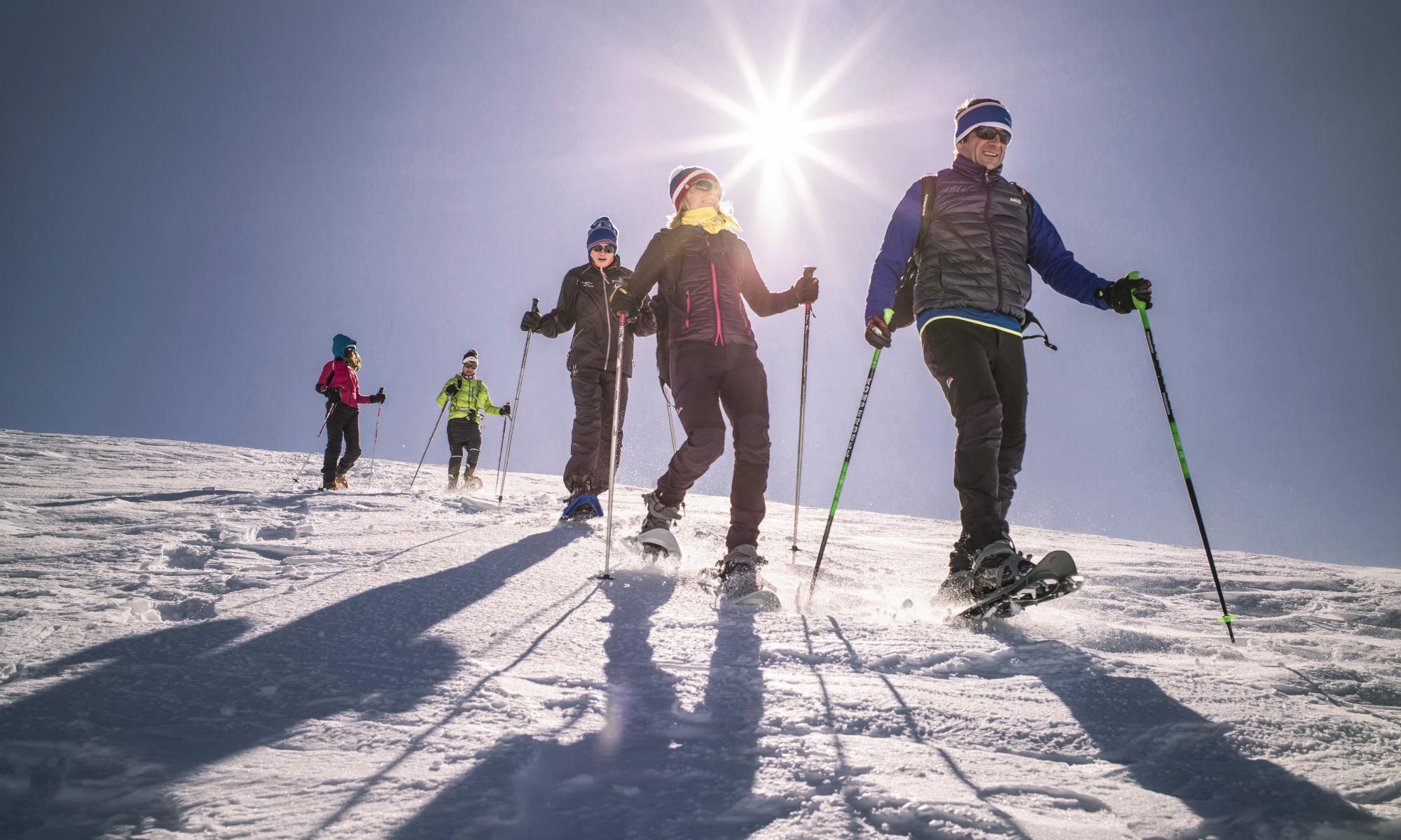 Auf einer sonnigen Piste in Verbier sind 5 Schneeschuhwanderer unterwegs.