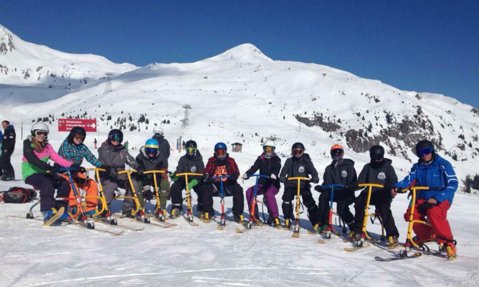 Eine Gruppe von Jugendlichen und ein Skilehrer sitzen auf Snowbikes auf einer sonnigen Piste im Skigebiet Arosa.