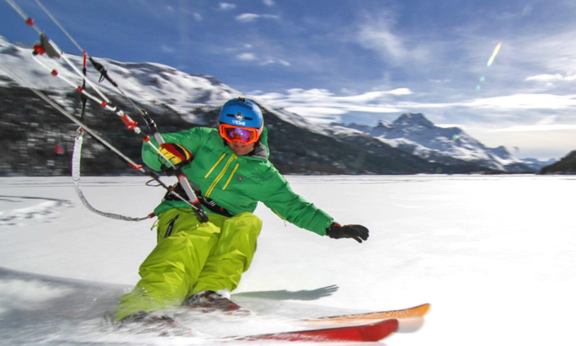 Ein Skifahrer lässt sich von einem Kite über die Piste in der Ferienregion Engadin St. Moritz ziehen.