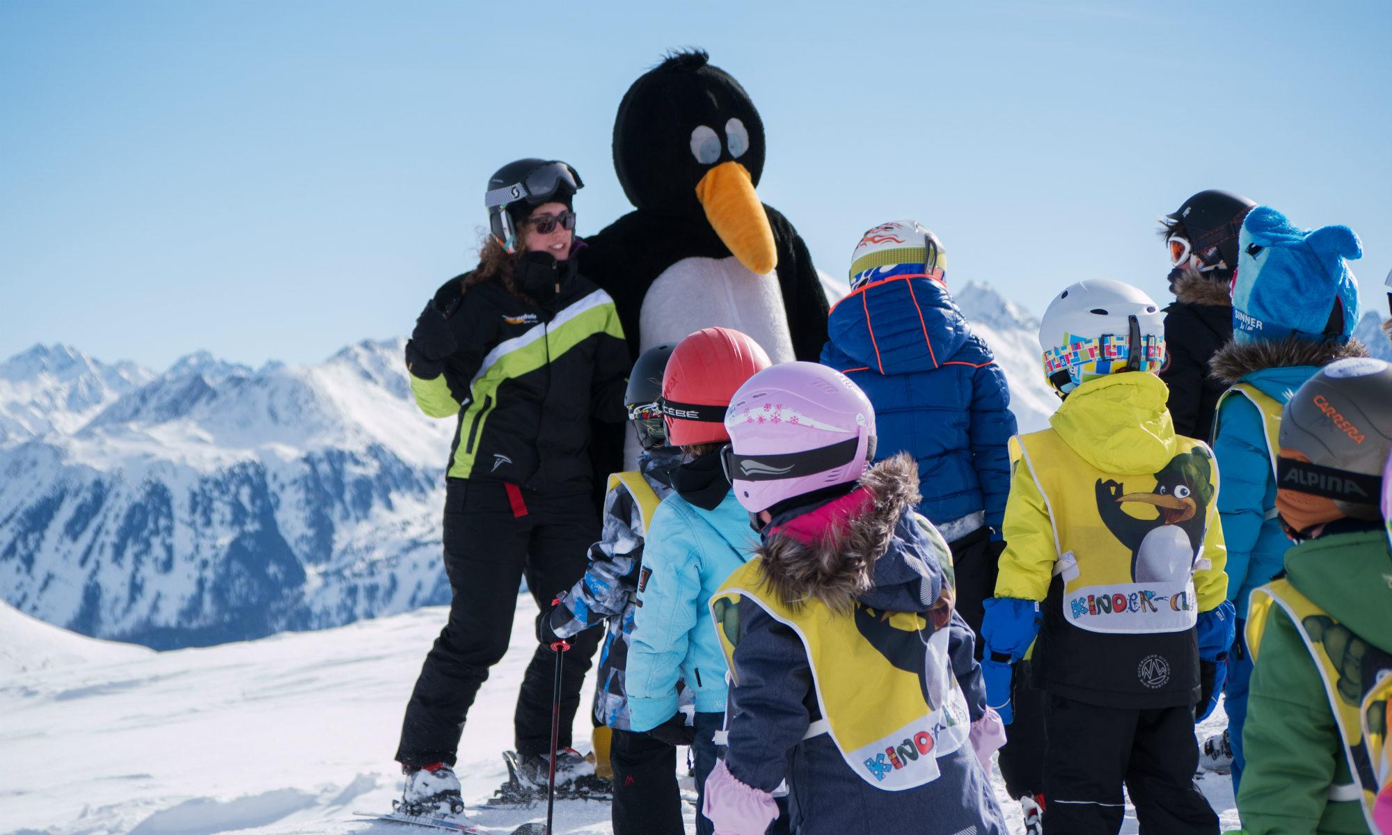 Un cours de ski pour débutants avec une mascotte.