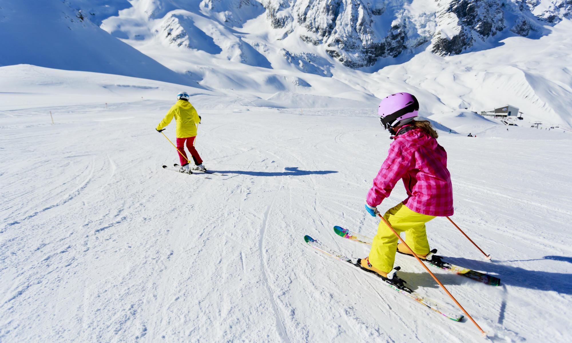 Une jeune skieuse suit son moniteur sur une piste de ski.