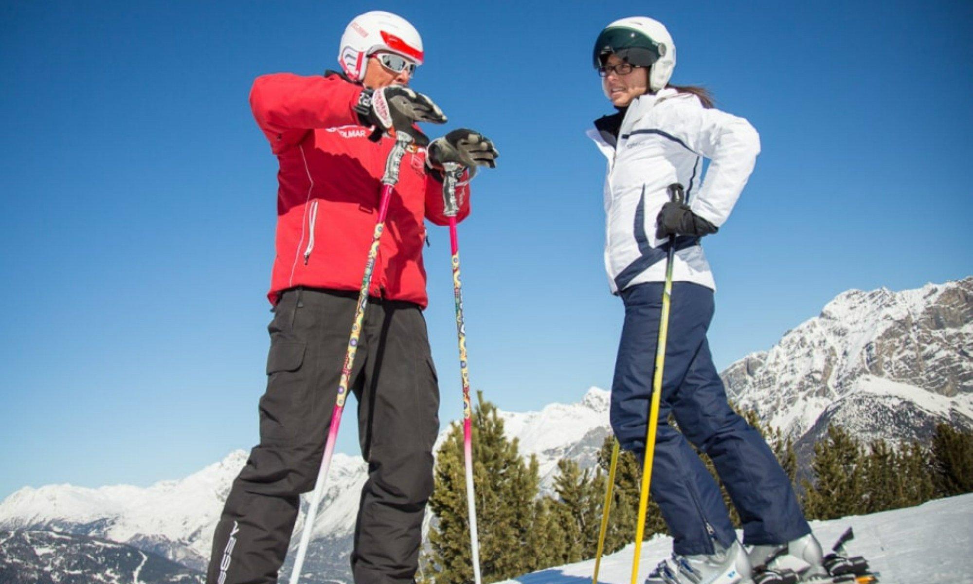 Un maestro privato di sci spiega un movimento alla sua alieva.