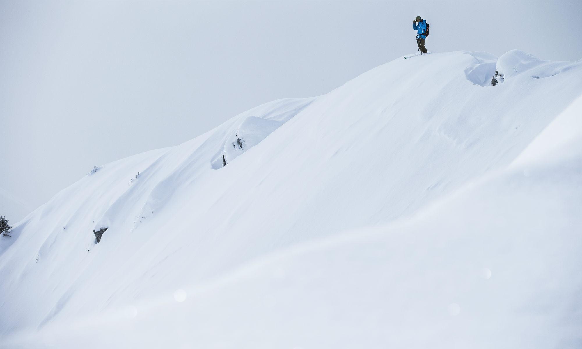 Skifahrer blickt von einer Wechte aus in einen tief verschneiten Hang in Laax.
