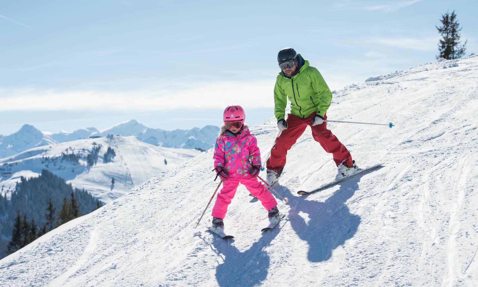 Ein Kind mit seinem Skilehrer auf einer Piste im Skigebiet Kitzbühel.