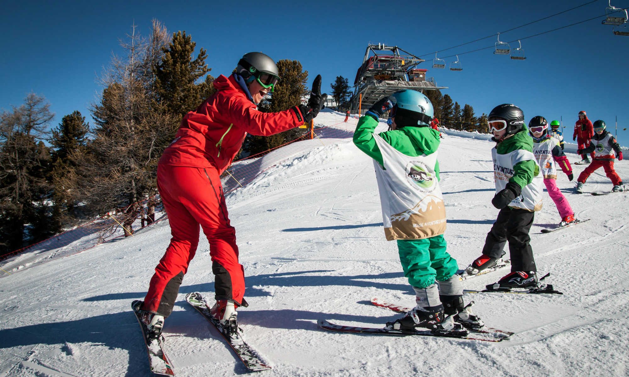 Eine gut gelaunte Skilehrerin übt mit Kindern das Kurvenfahren auf einer Pisten in Nendaz.