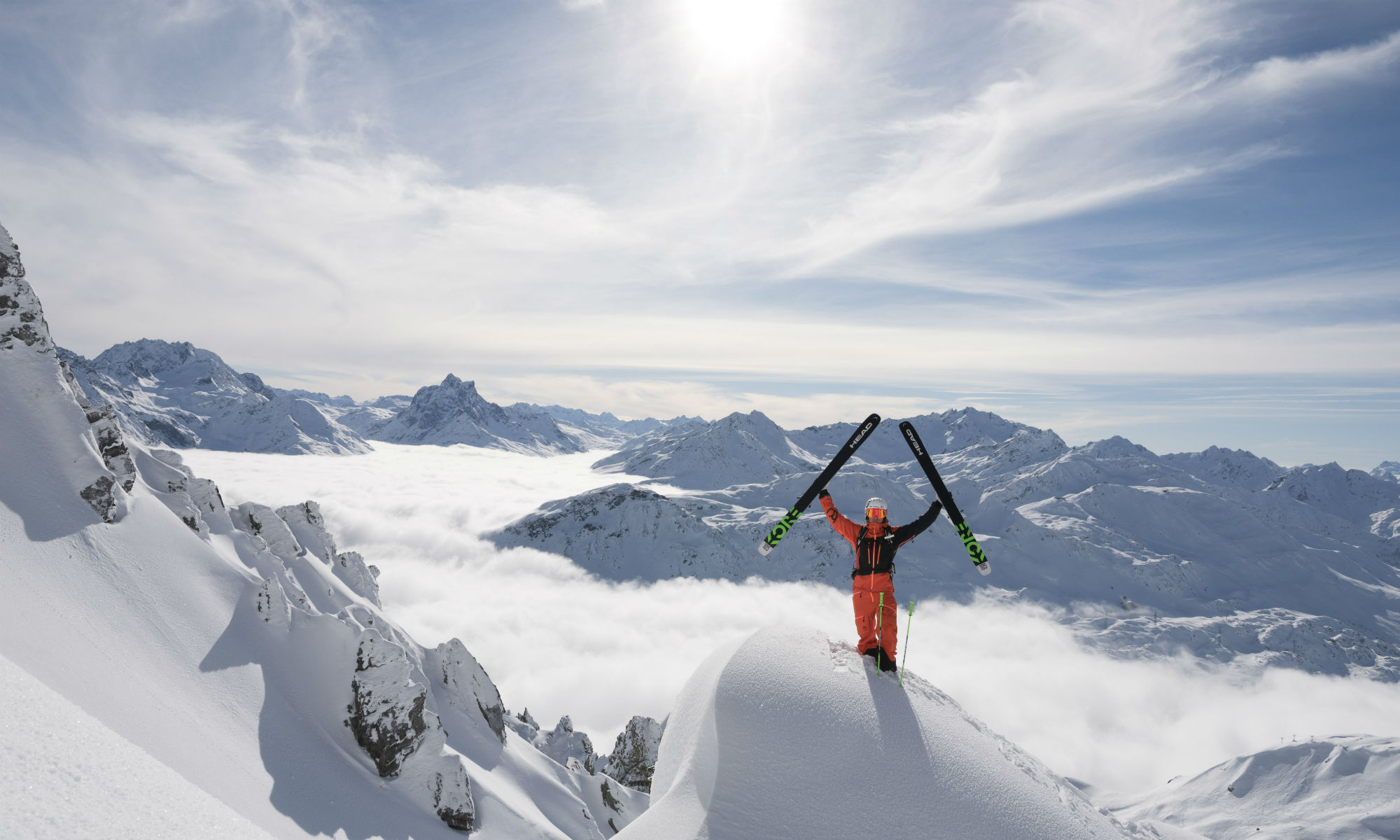 A freeride skier is posing on a ledge on the Arlberg in front of a snowy mountainous landscape.