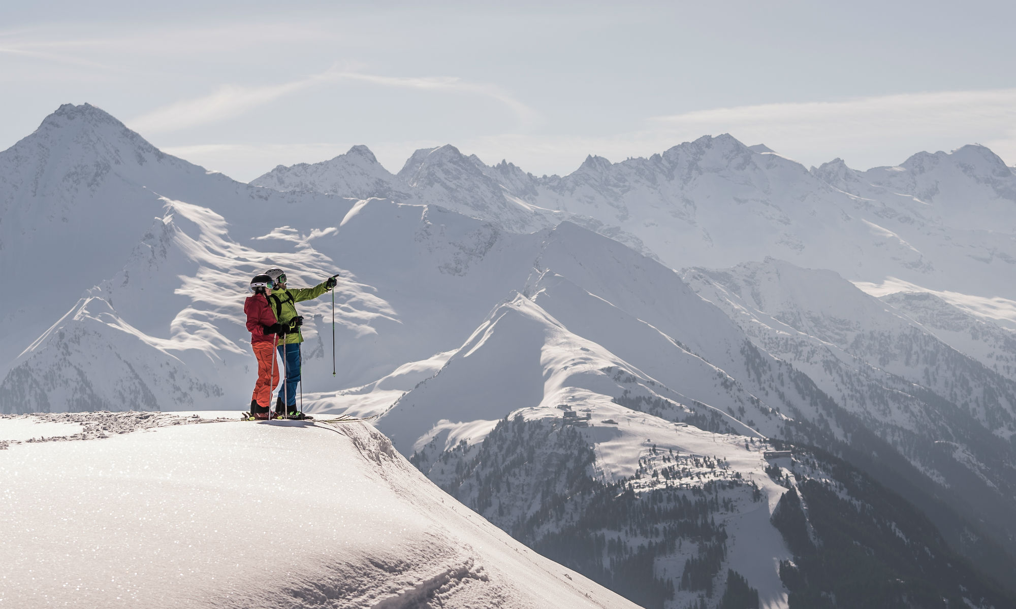 Two freeride skiers enjoying the view of the surrounding mountainous landscape in the Zillertal valley.