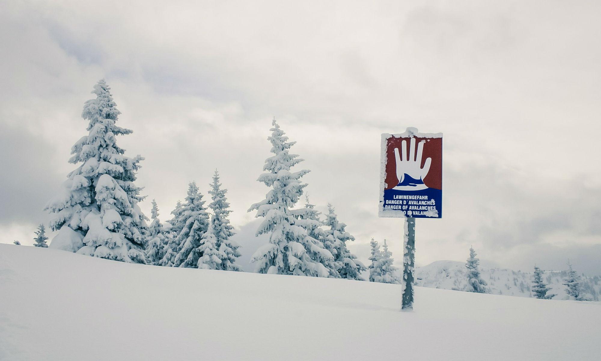 Ein Hinweisschild warnt vor der Lawinengefahr auf einer tief verschneiten Waldabfahrt.