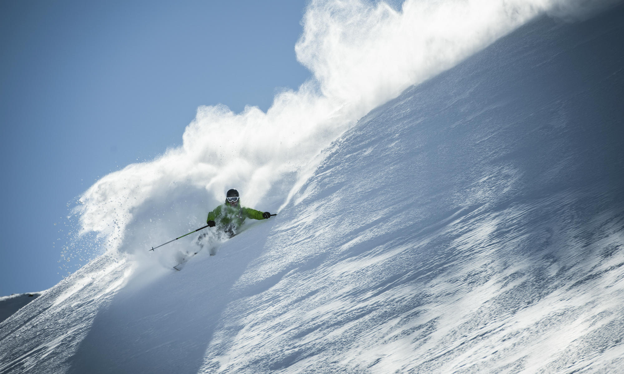 A freeride skier is skiing in deep powder snow.