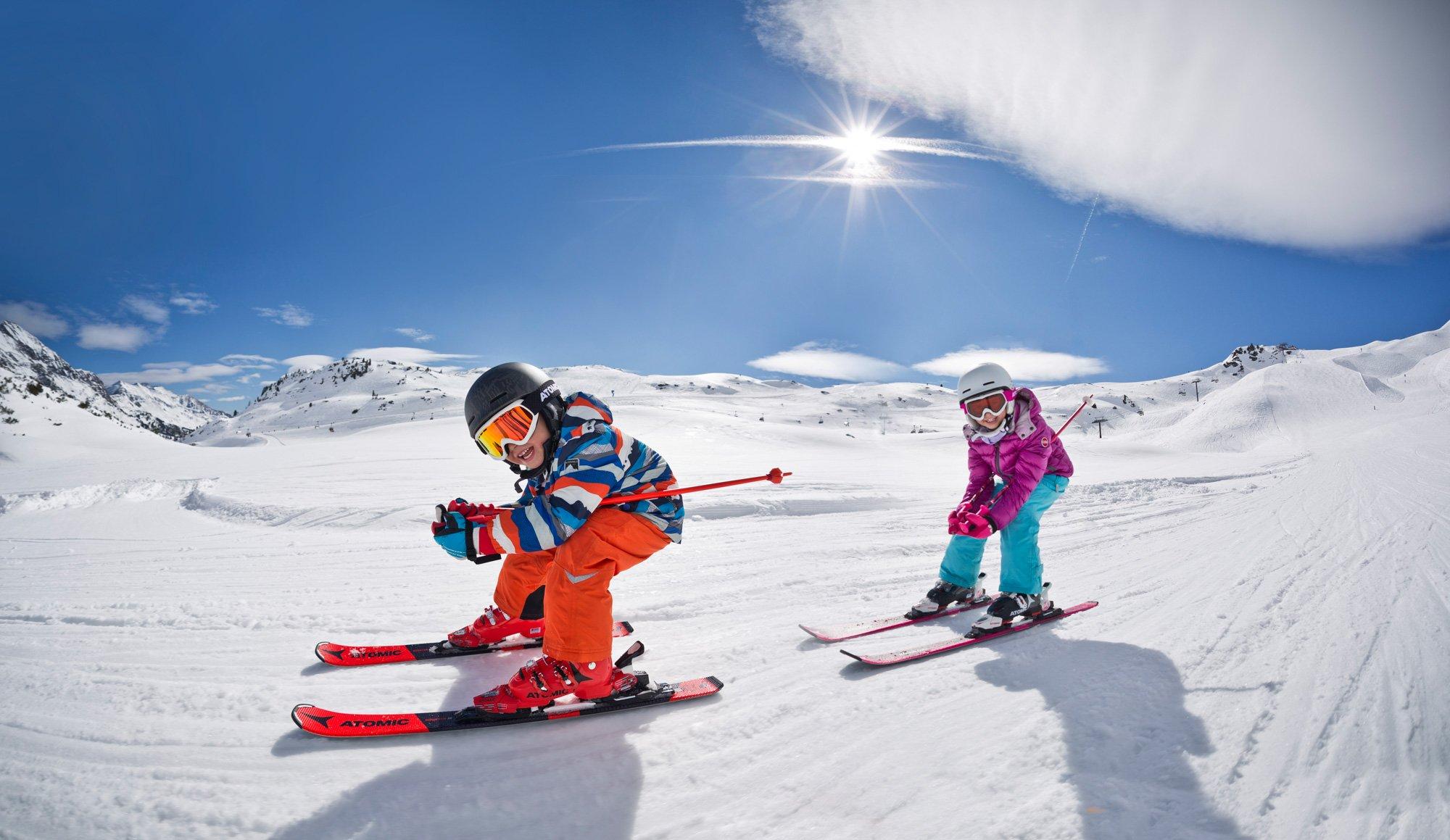 Zwei Kinder mit ATOMIC Ski beim Skifahren auf einer sonnigen Piste.