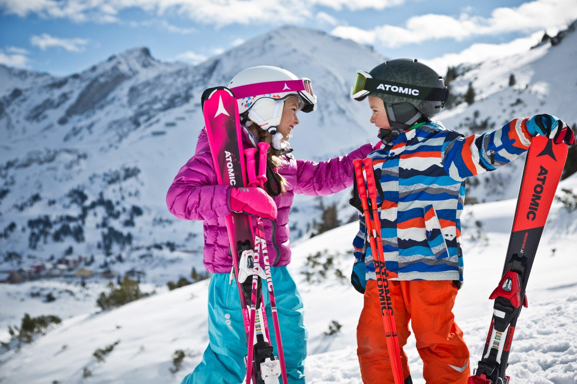 Zwei Kinder mit ihren ATOMIC Ski auf einer verschneiten Piste.