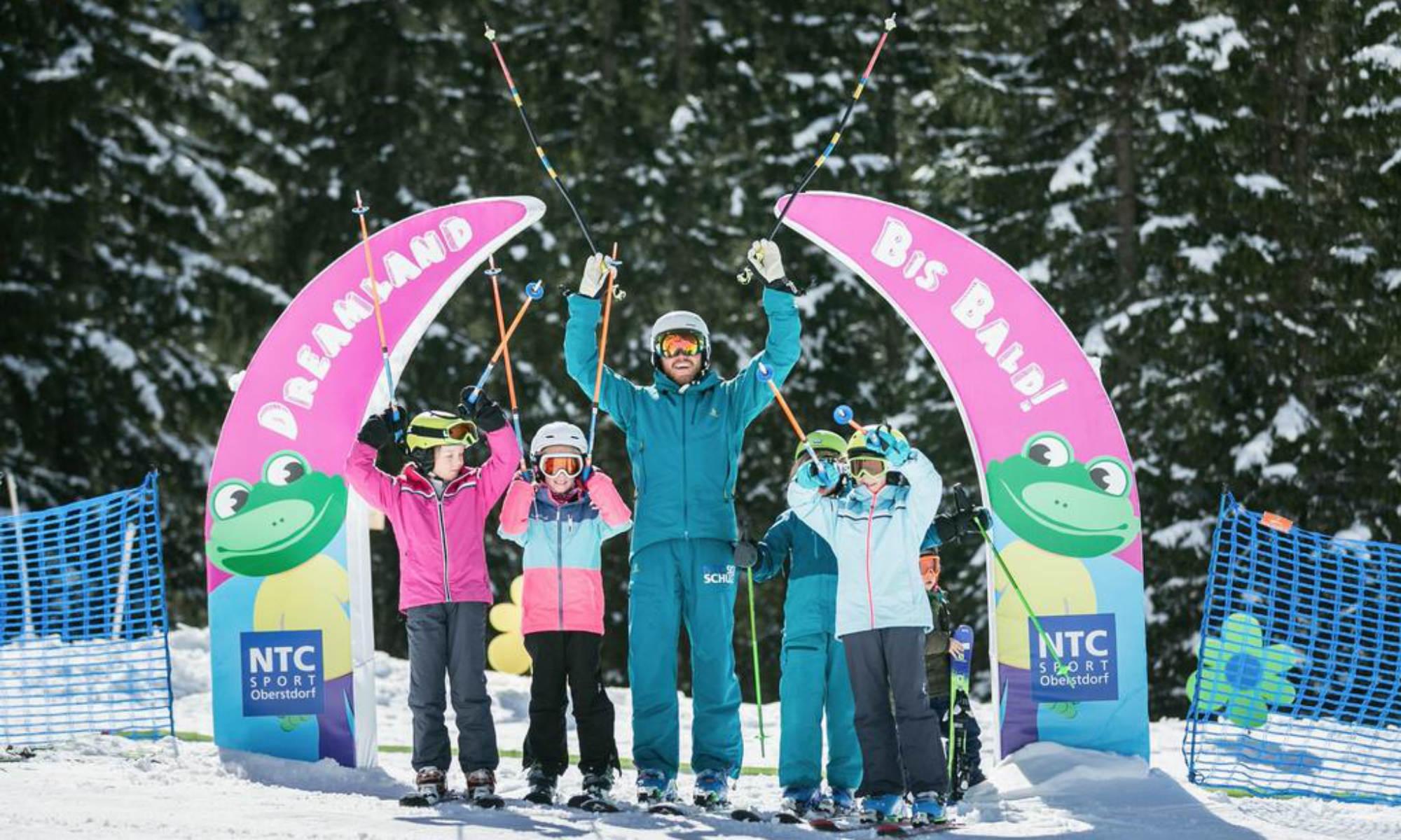 Kinder mit einem Skilehrer vor dem Dreamland der NTC SPORTS Skischule Oberstdorf.