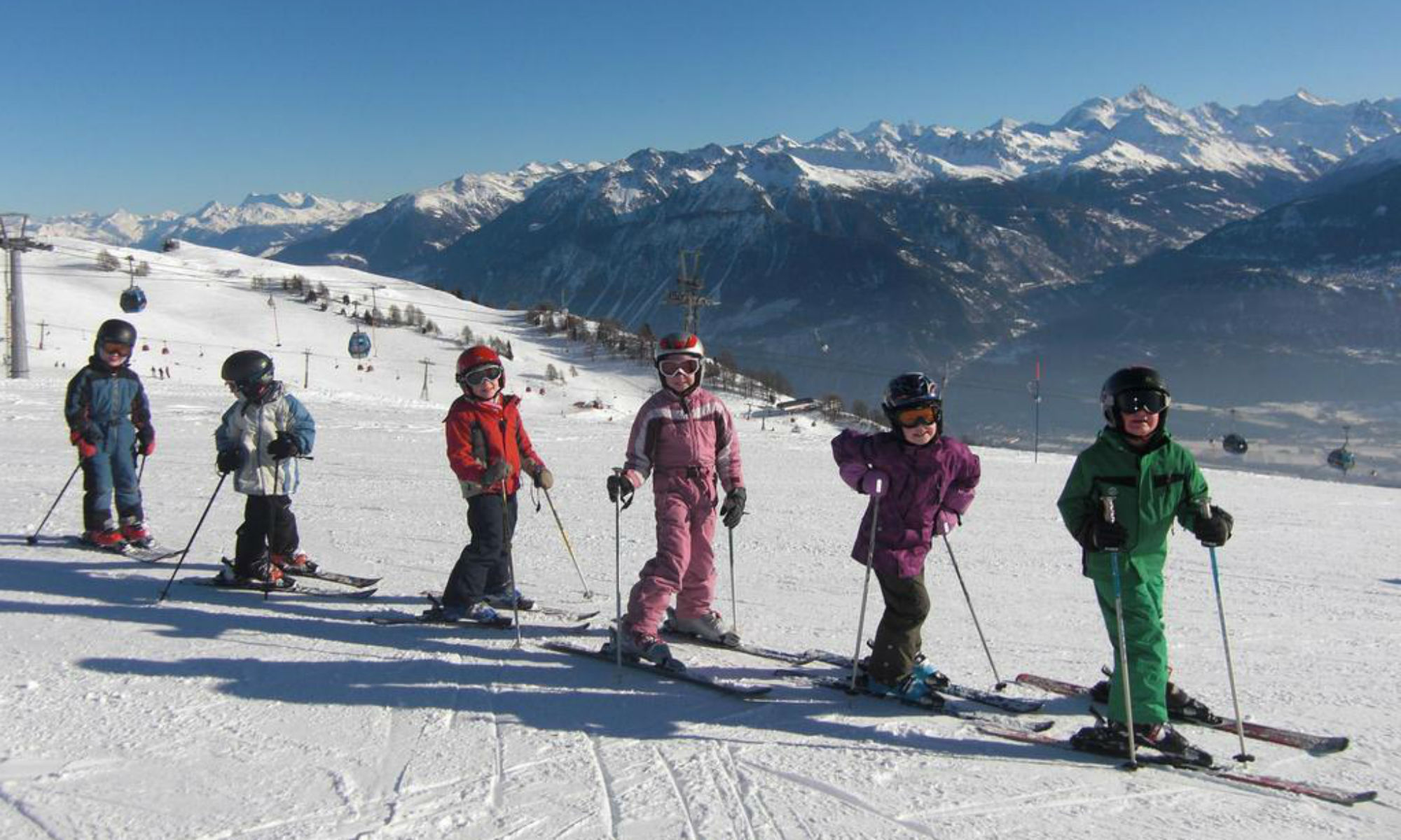Eine Gruppe von Kinder beim beim Skifahren lernen im Wallis auf einer sonnigen Piste in Crans-Montana.