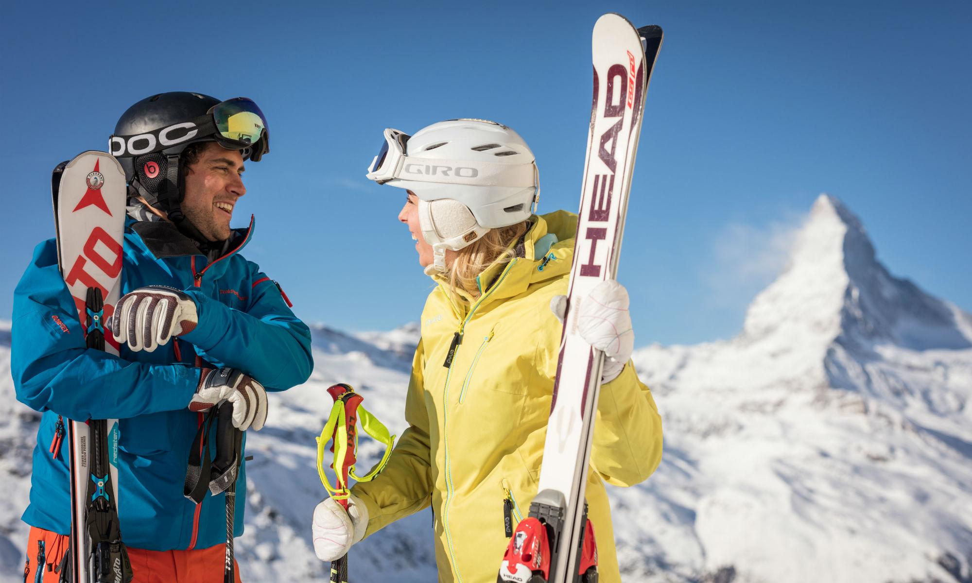 Zwei Skifahrer lachen und unterhalten sich vor dem Gipfel des Matterhorns.
