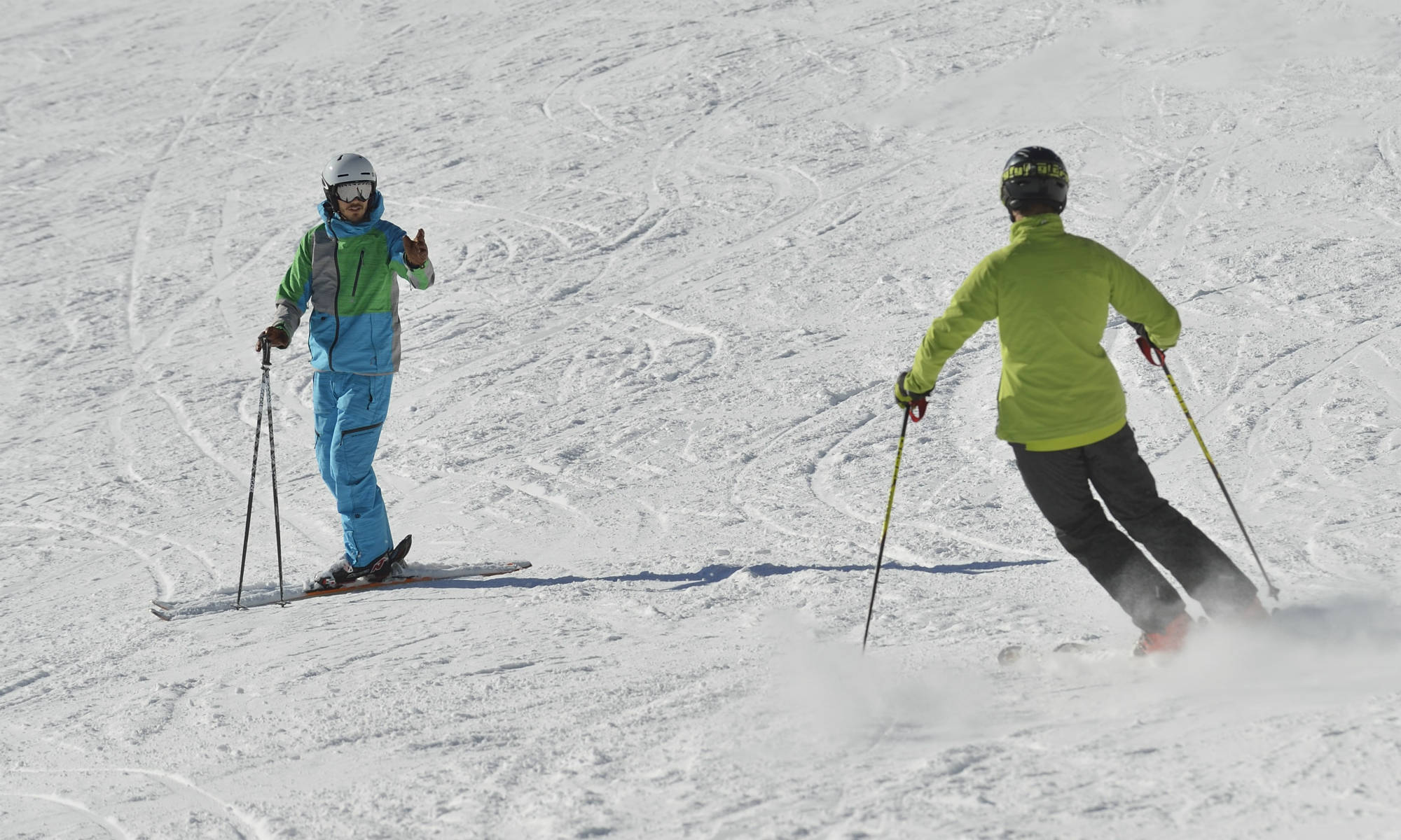 A ski instructor and a beginner are practising the parallel turn together on a ski slope.