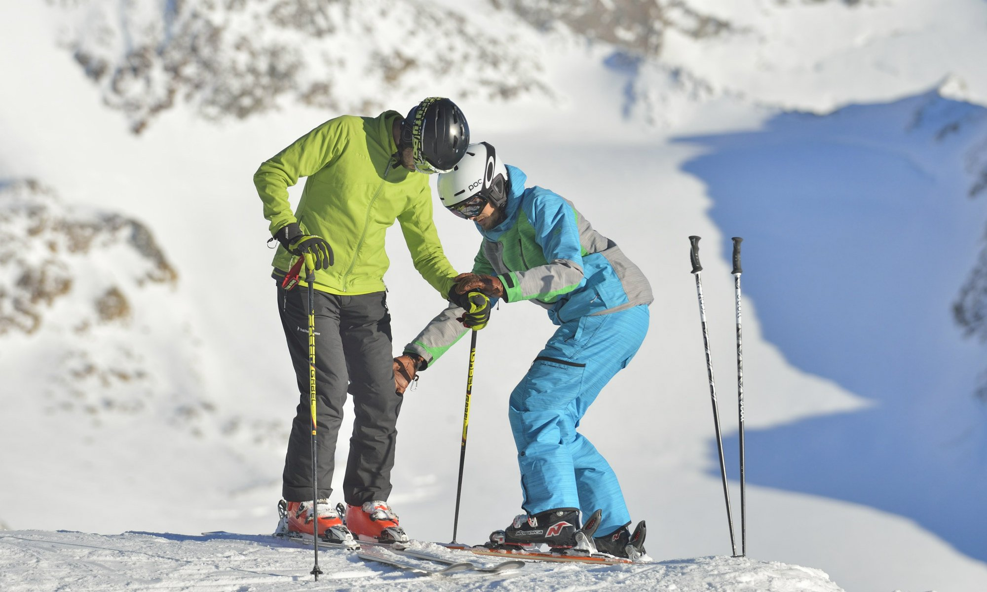 A ski instructor is showing a skier how to position the legs.