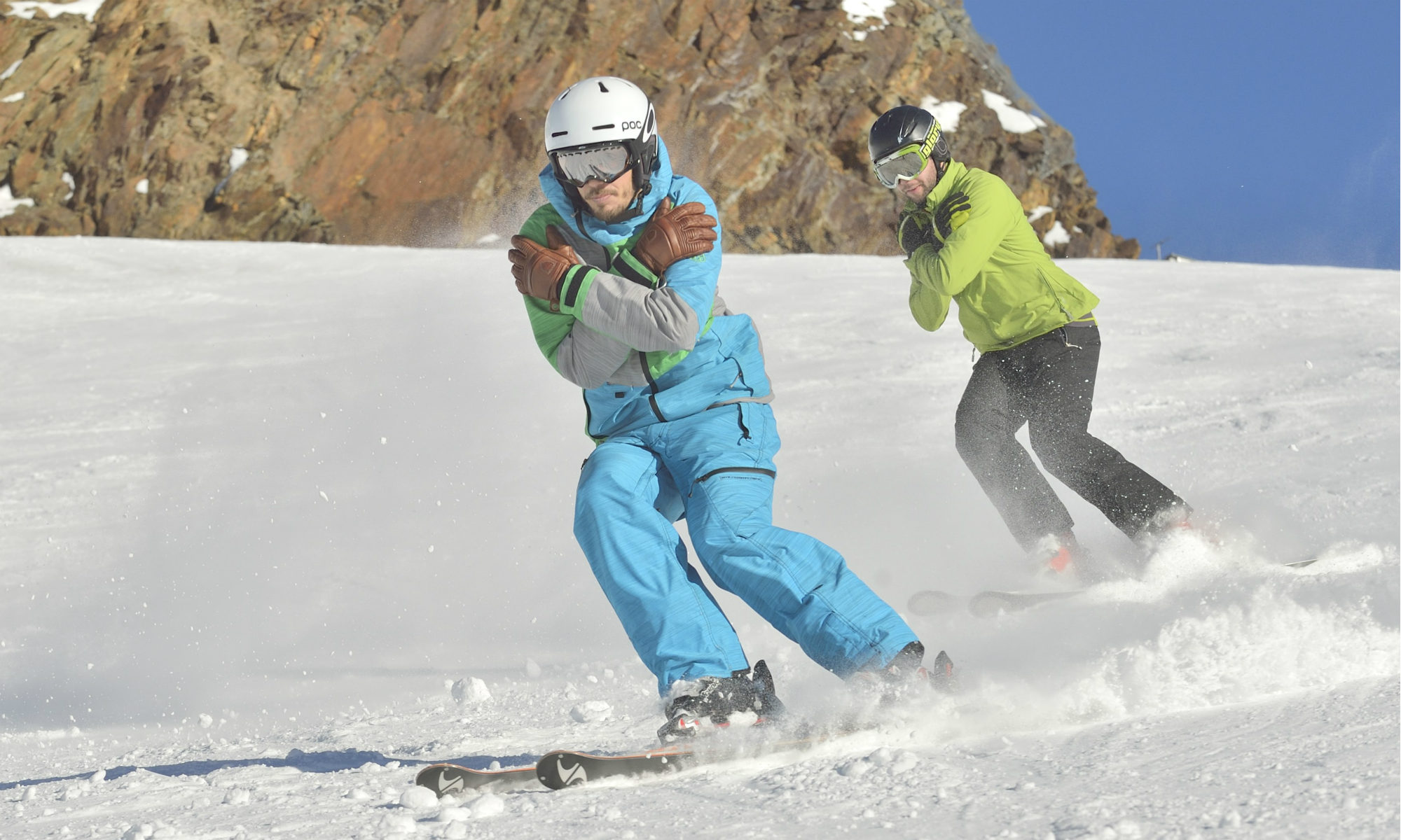 Two skiers practising the weight transfer while skiing.