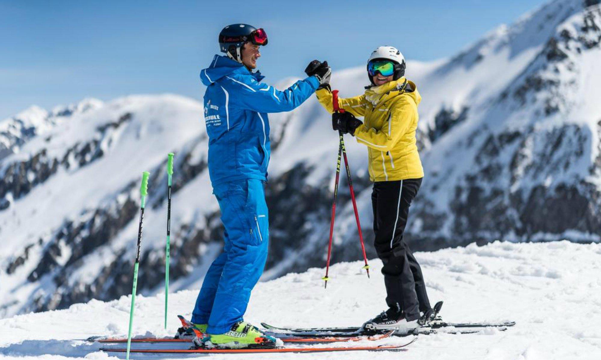 Ein Skilehrer und eine Skifahrerin stehen auf einer sonnigen Piste mit Blick auf das Bergpanorama im Skigebiet Flachau.