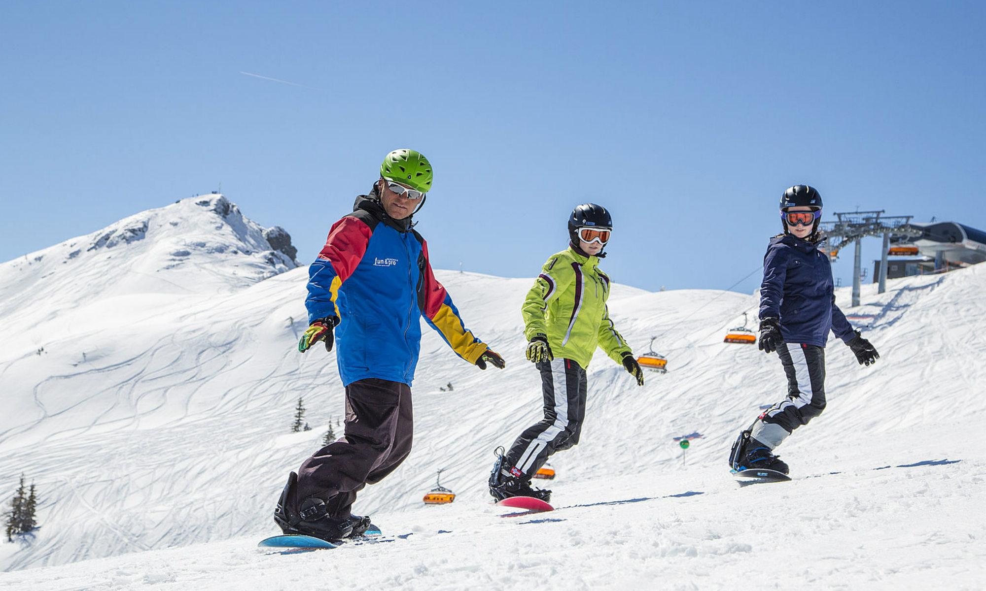 Ein Snowboardlehrer und 2 Jugendliche fahren auf einer sonnigen Piste im Skigebiet Flachau.