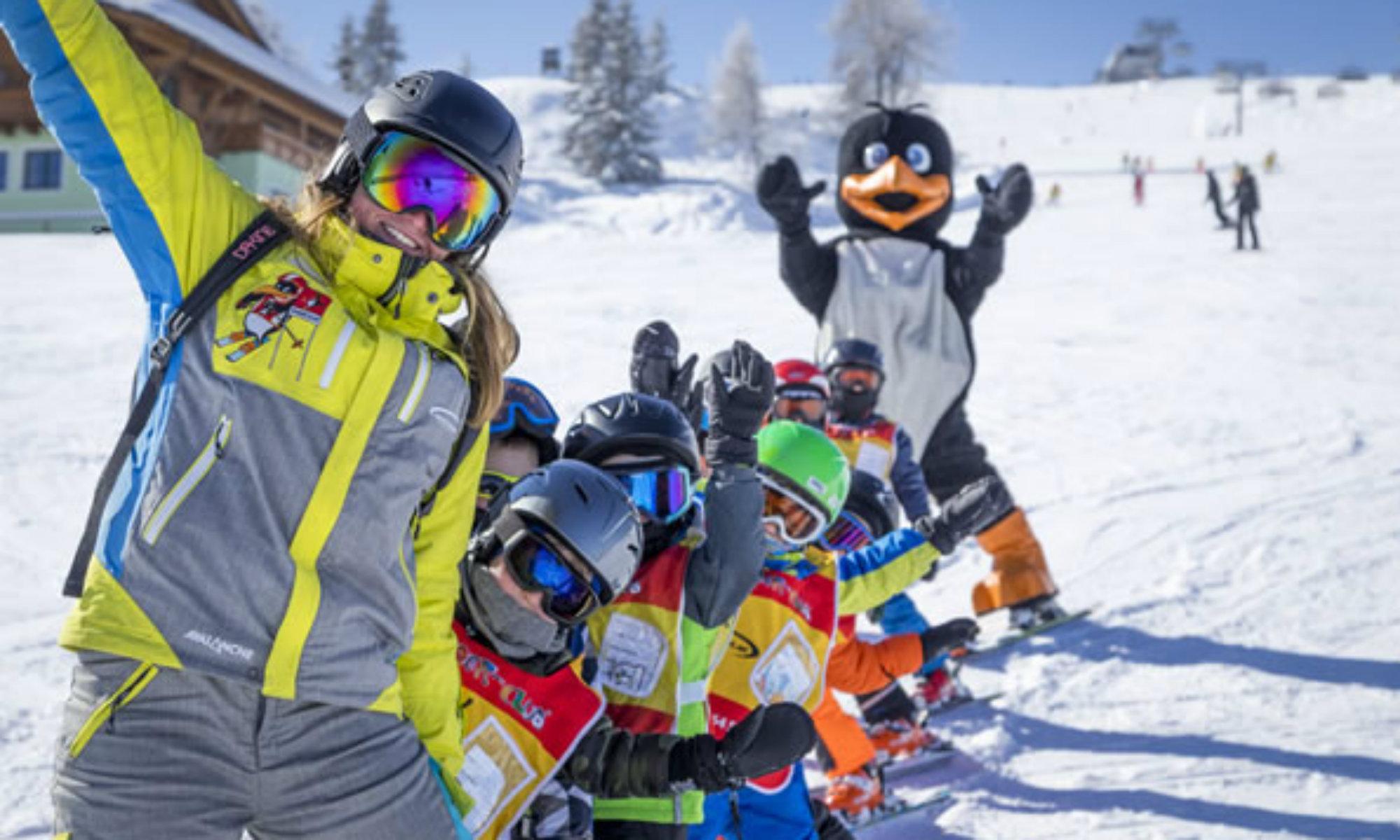 Eine Skilehrerin der Skischule Sport am Jet Flachau, eine Gruppe Kinder und ein Pinguin Maskottchen stehen auf einer sonnigen Piste im Skigebiet Flachau.