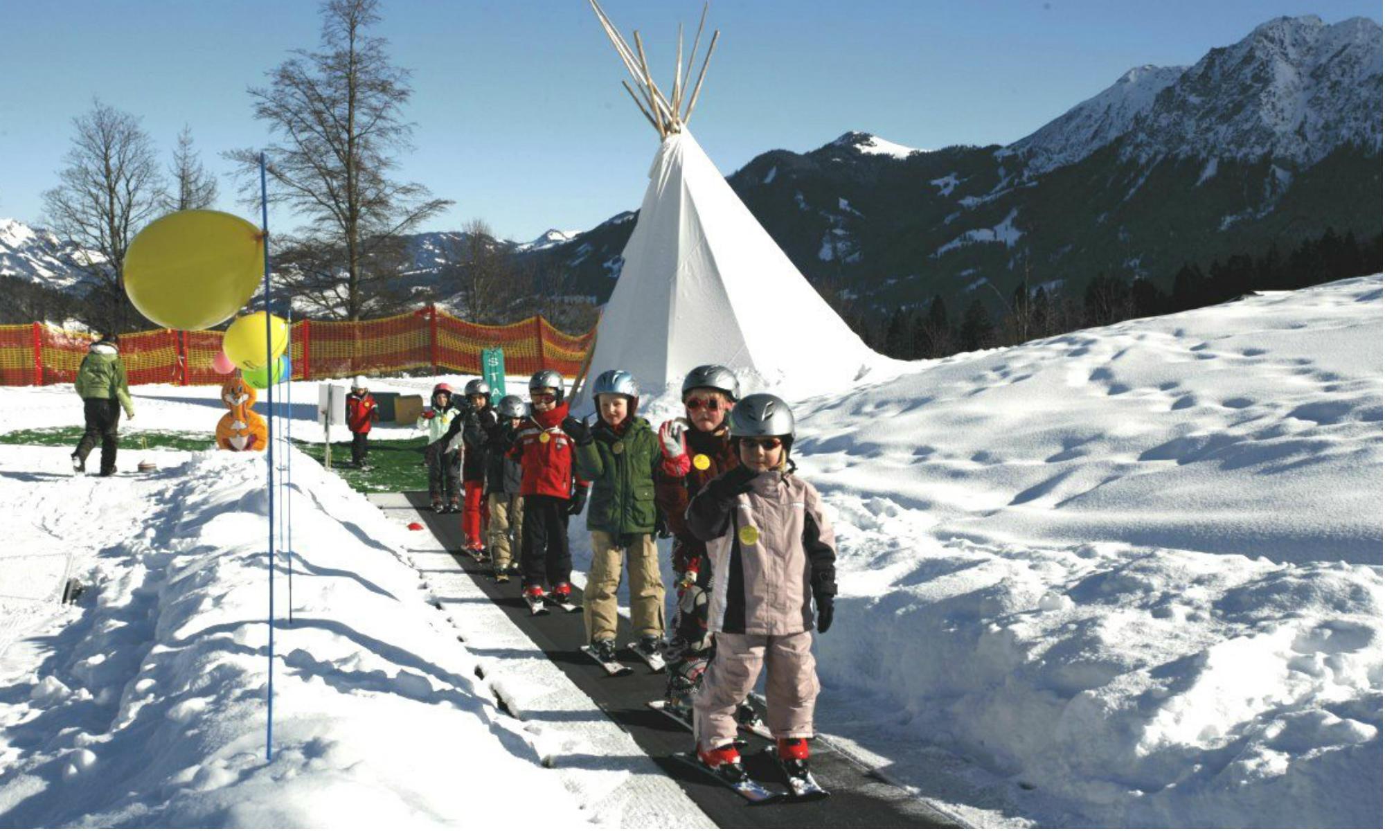 Kinder auf dem Zauberteppich im Kinderland der Alpin Skischule in Oberstdorf.