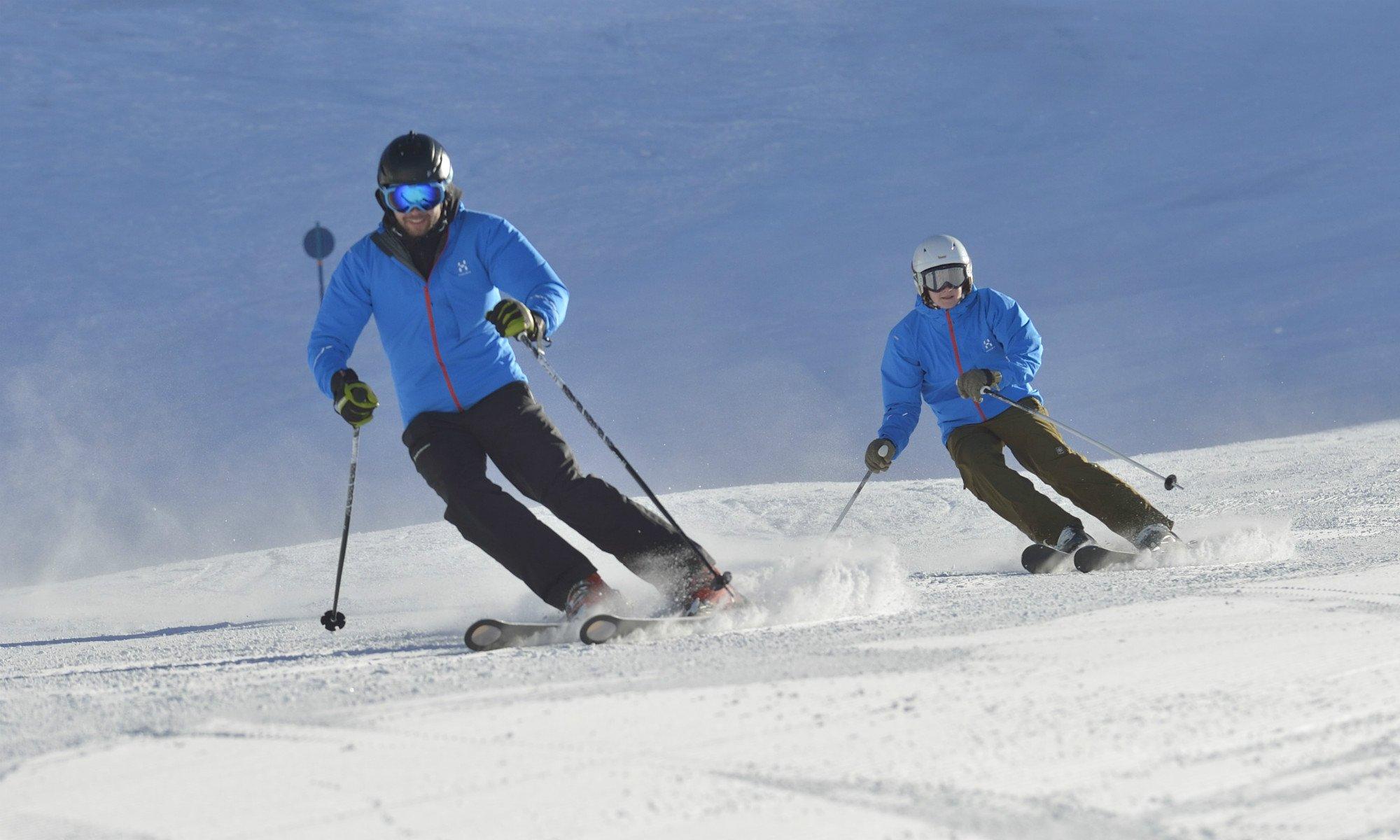 Zwei Skifahrer fahren im Parallelschwung die Skipiste hinunter.