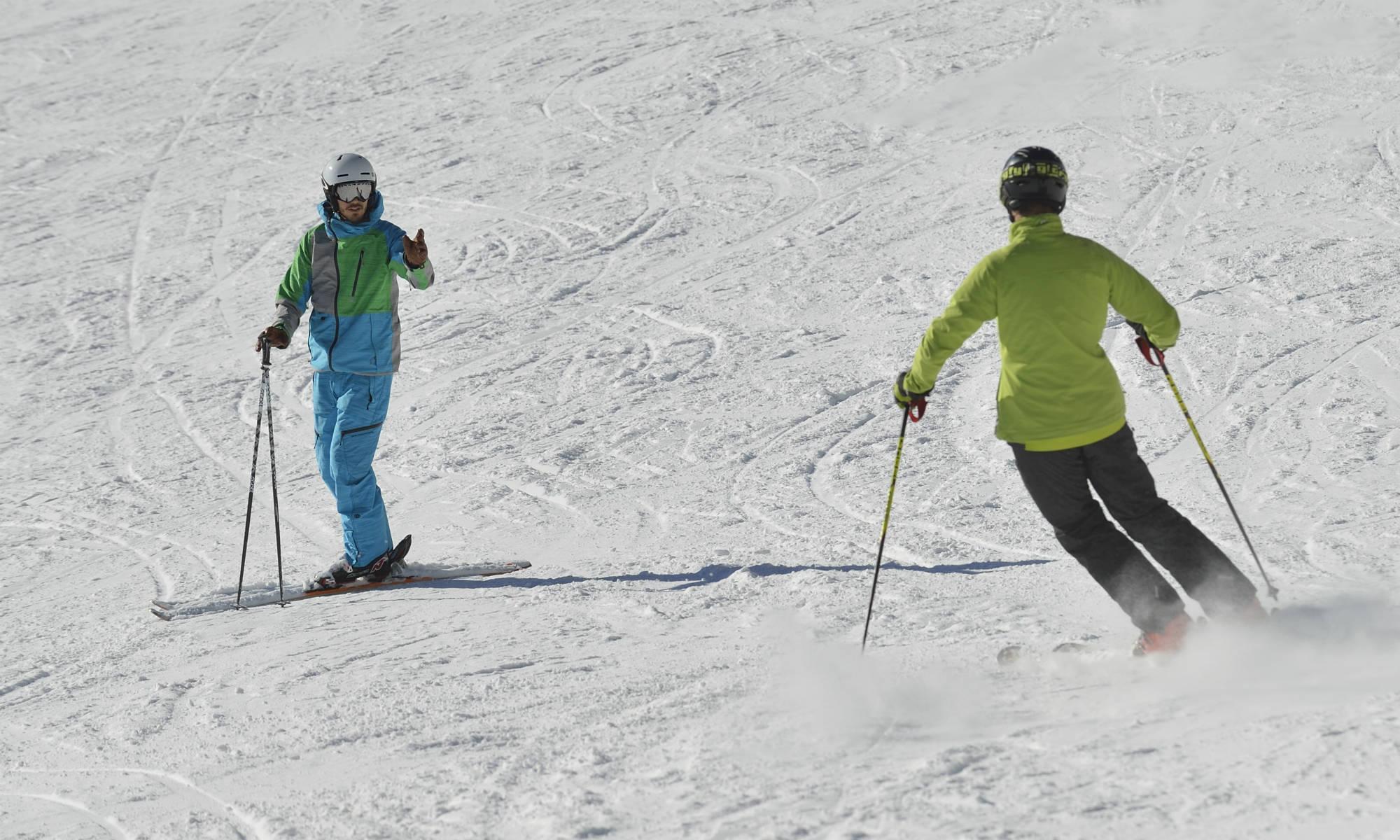 Ein Skilehrer und ein Kursteilnehmer üben gemeinsam den Parallelschwung auf einer Skipiste.