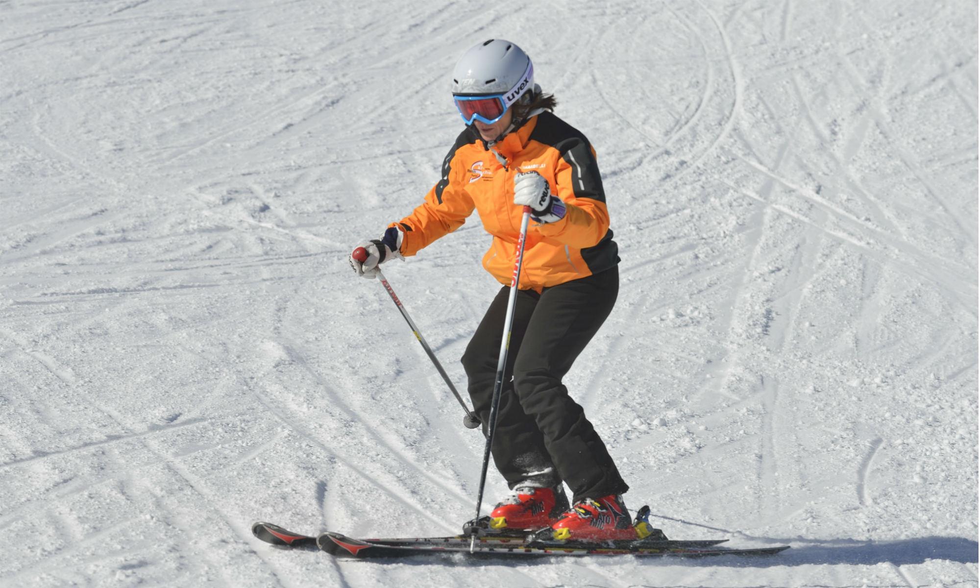 Ingrid Salvenmoser zeigt den richtigen Stockeinsatz beim Parallelschwung auf einer sonnigen Skipiste vor.